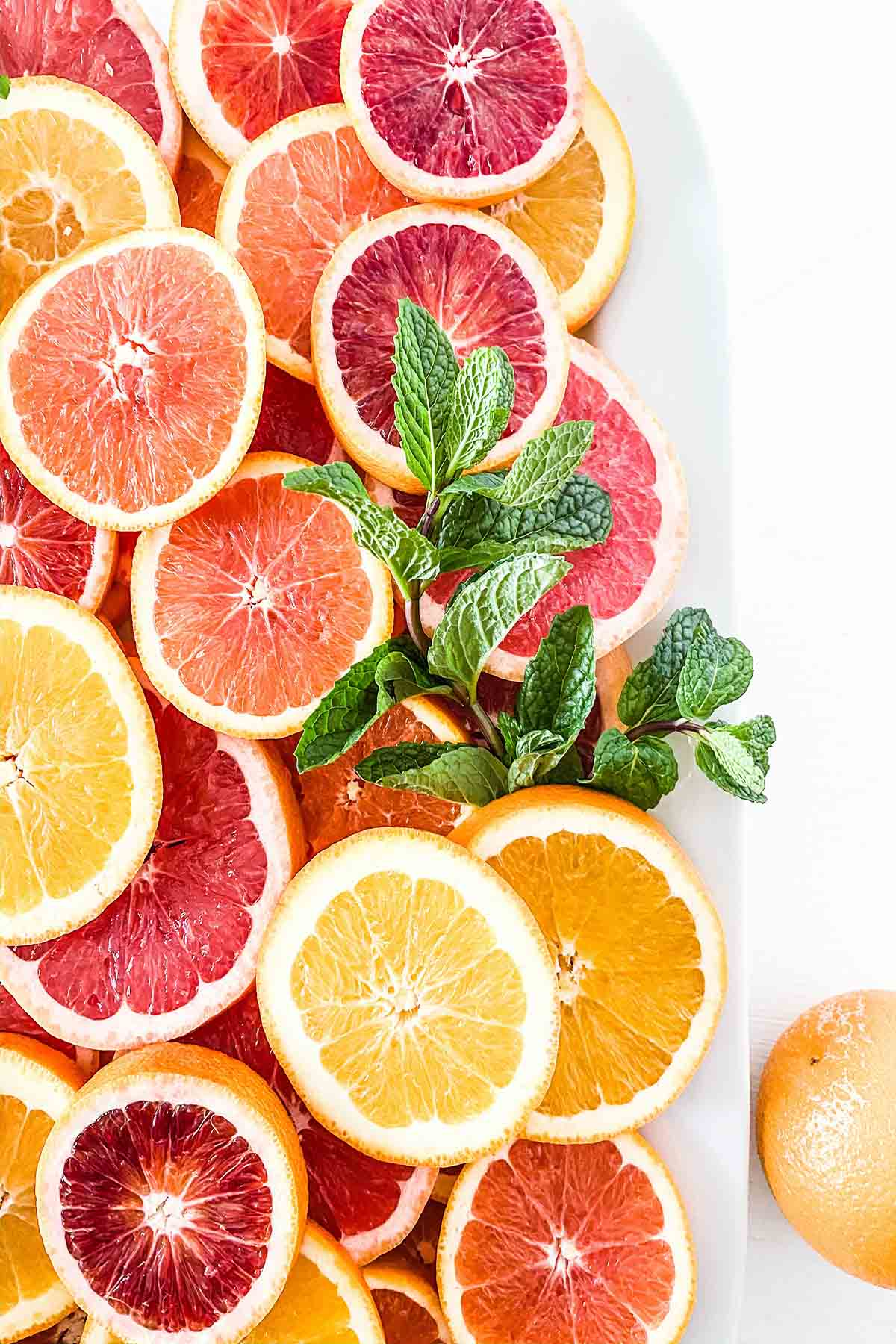 Several slices of citrus fruit on a plater including blood orange, orange, and grapefruit.