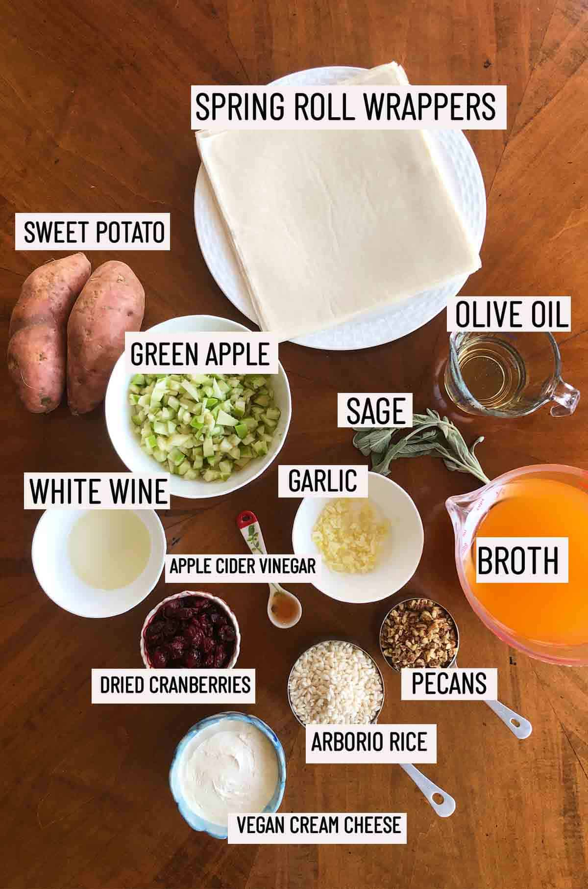 Birds eye view of portioned ingredients needed to make baked spring rolls including cream cheese, arborio rice, pecans, both, dried cranberries, apple cider vinegar, garlic, sage, olive oil, white wine, green apple, sweet potato, and spring roll wrappers.