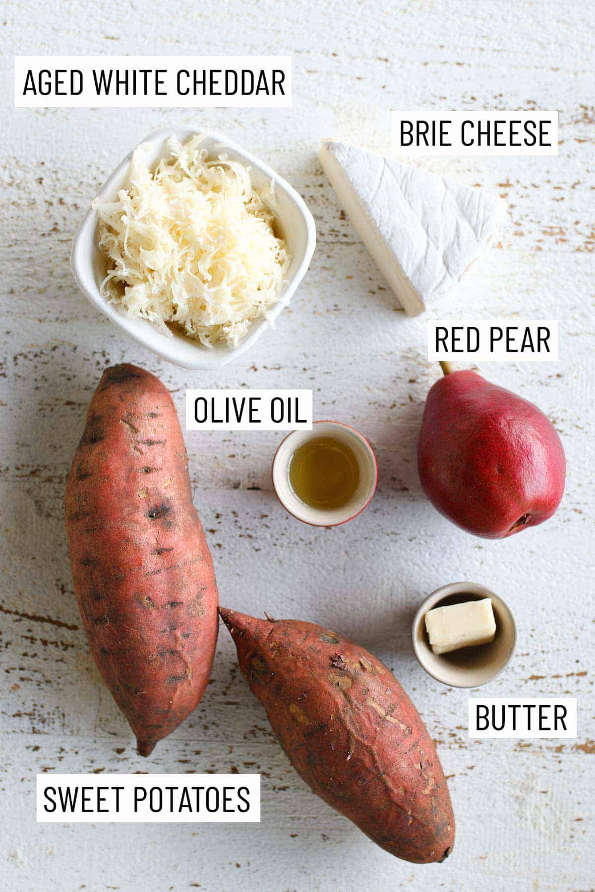 Overhead image of ingredients needed to make the recipe: sweet potatoes, aged white cheddar, bri cheese, olive oil, red pear, and butter.
