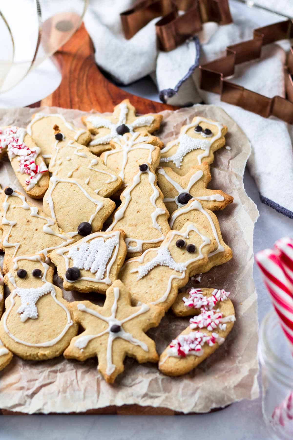 Several gluten free Christmas cookies sitting on parchment paper with Christmas cookie cutters and candy canes in the background.