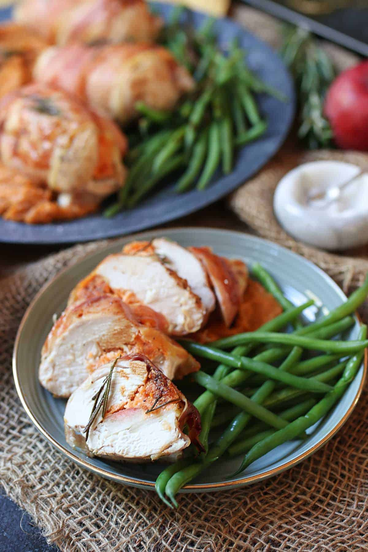Complete holiday recipe cut in four pieces on a blue plate with green beans on the side.