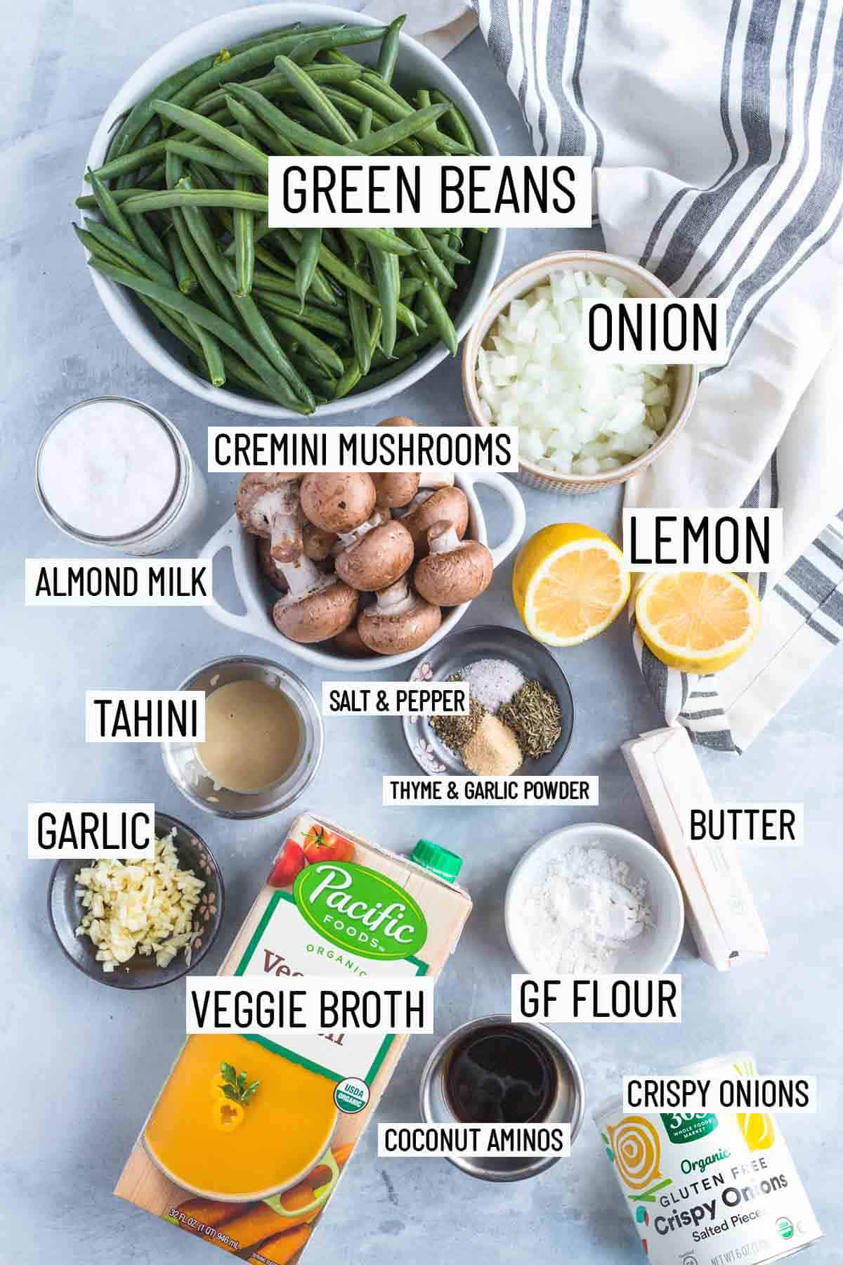 Flat lay image of portioned recipe ingredients including onion, lemon, mushroom, almond milk, green beans, tahini, spices, butter, flour, veggie broth, garlic, coconut aminos, and crispy onions.