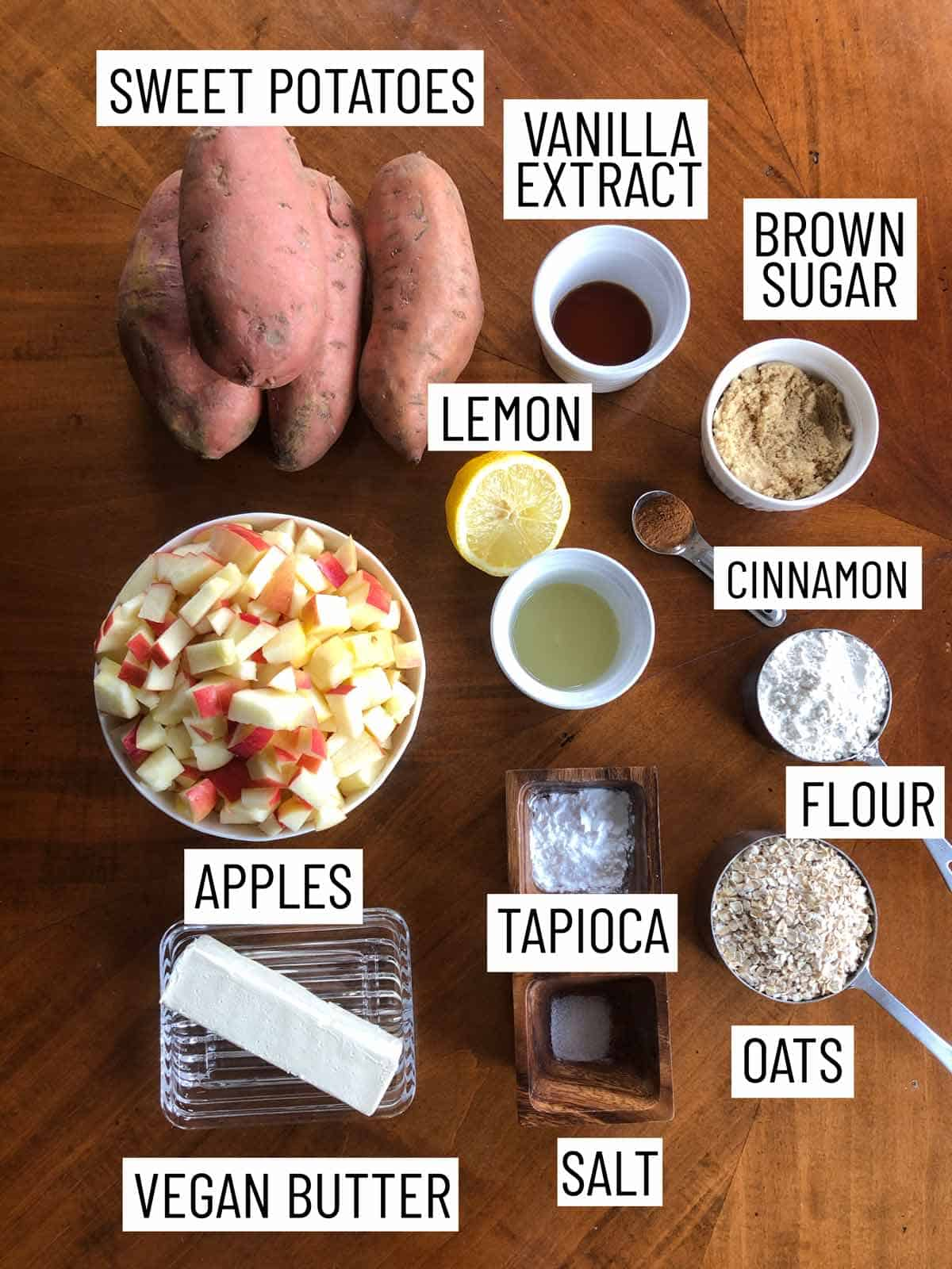 Overhead photo of ingredients containing yams, vanilla extract, brown sugar, cinnamon, lemon, flour, apples, tapioca, oats, salt, and vegan butter.