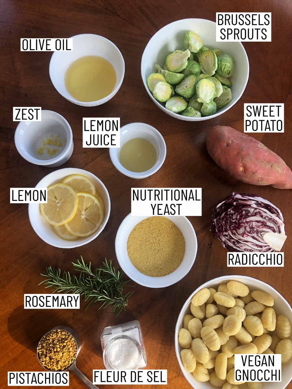 Flat lay image of portioned recipe ingredients including sweet potato, radicchio, vegan gnocchi, fleur de sel, pistachios, rosemary, lemon, nutritional yeast, olive oil, and brussels sprouts.