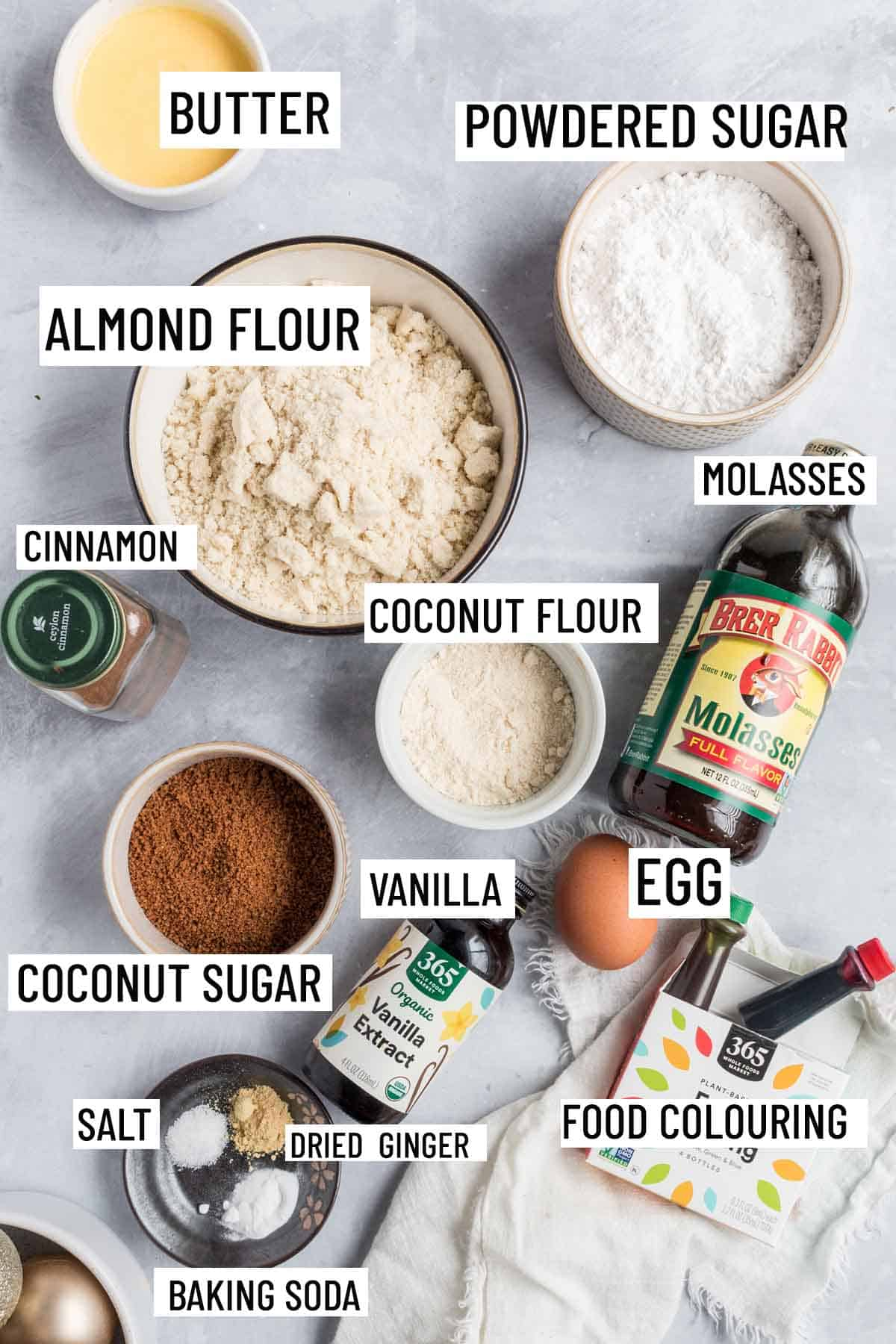 Birds eye view of portioned recipe ingredients including almond flour, icing sugar, coconut flour, coconut sugar, cinnamon, egg, molasses, food colouring, dried ginger, salt, baking soda, butter and vanilla.