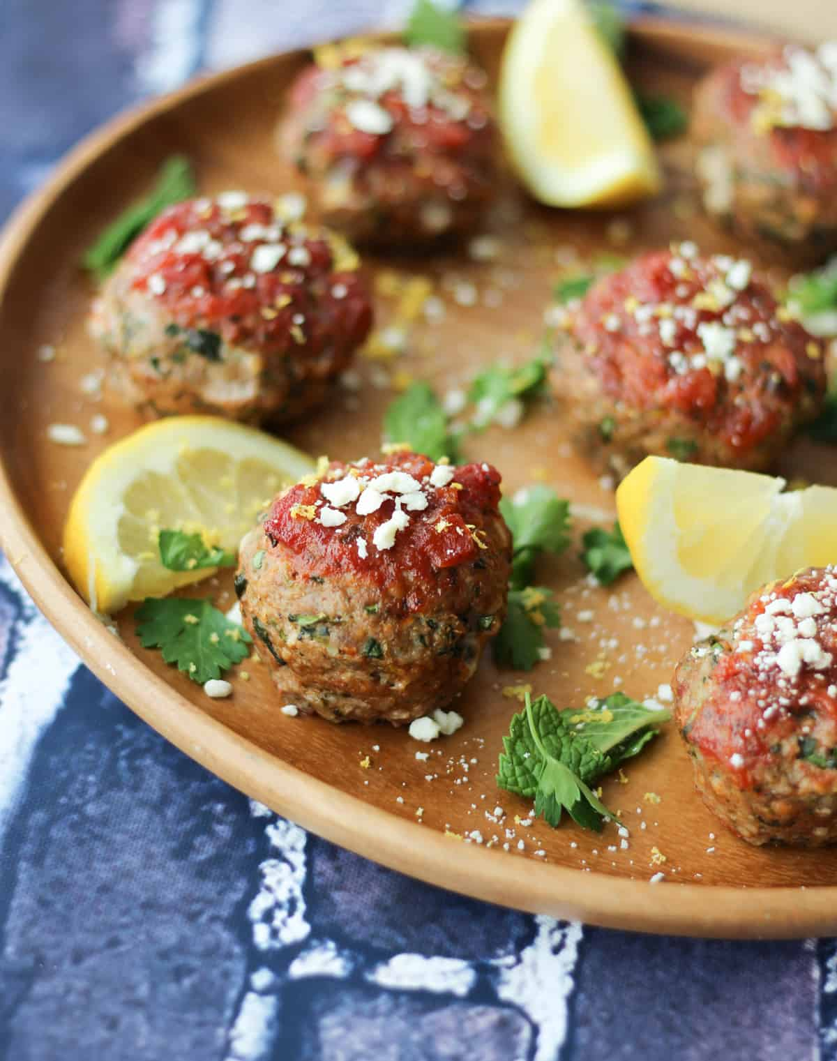 Close up of Greek meatballs topped with tomato sauce and feta, garnished with mint and lemon wedges.