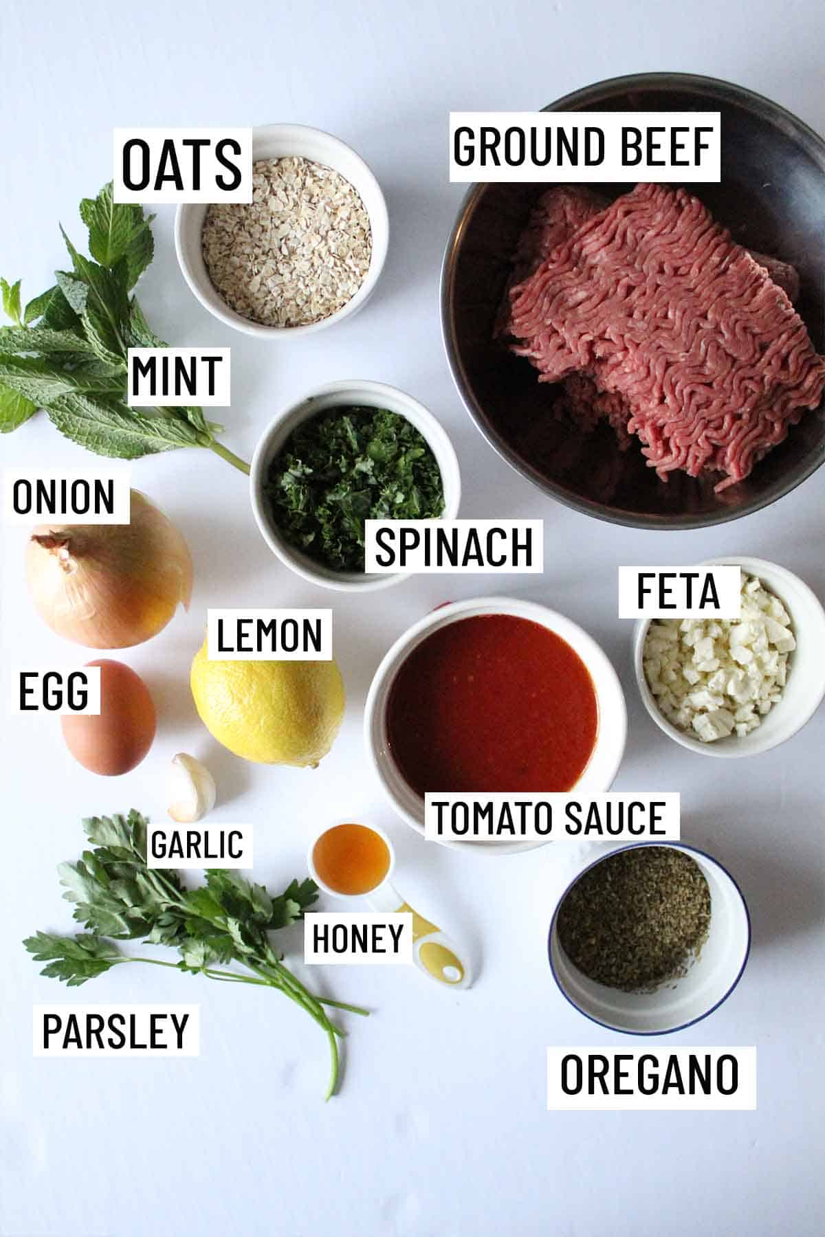 Birds eye view of portioned recipe ingredients for meatloaf muffins including ground beef, lemon, onion, garlic, egg, oregano, mint, parsley, oats, honey, feta, spinach and tomato sauce.