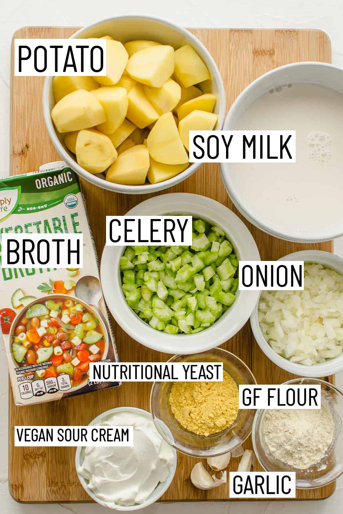 Flat lay image of portioned ingredients for potato soup including nutritional yeast, flour, sour cream, garlic, onion, celery, broth, soy milk, and potato.