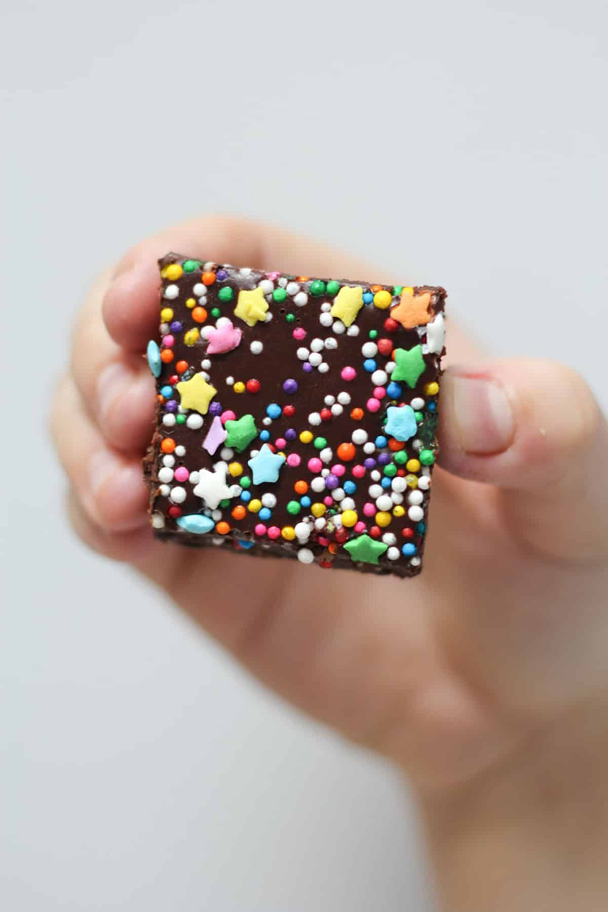 Hand holding up a no bake brownie square with rainbow sprinkles.