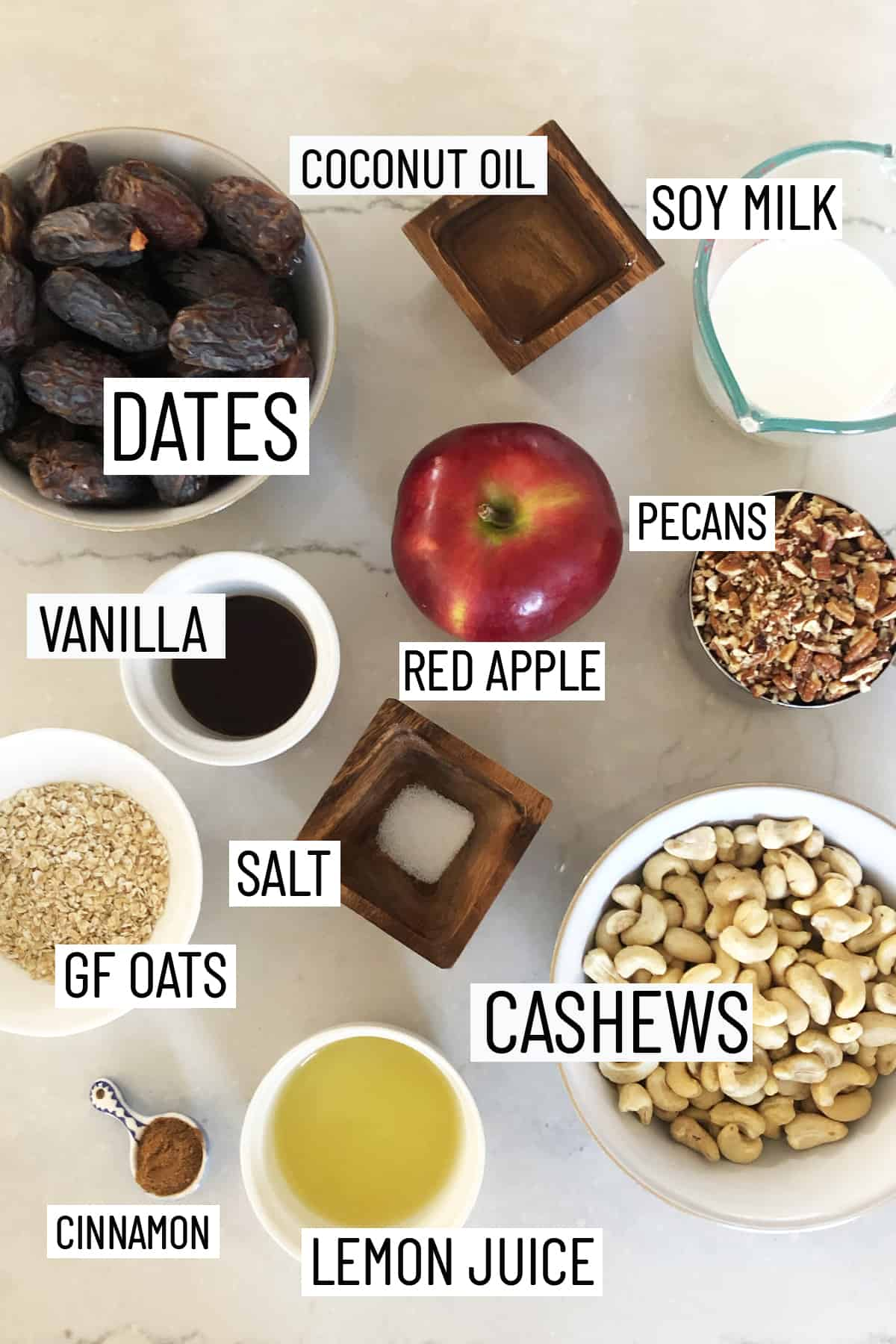 Flat lay image of portioned ingredients of raw vegan cheesecake including lemon juice, cinnamon, cashews, salt, oats, pecans, red apple, dates, vanilla, soy milk, and coconut oil.
