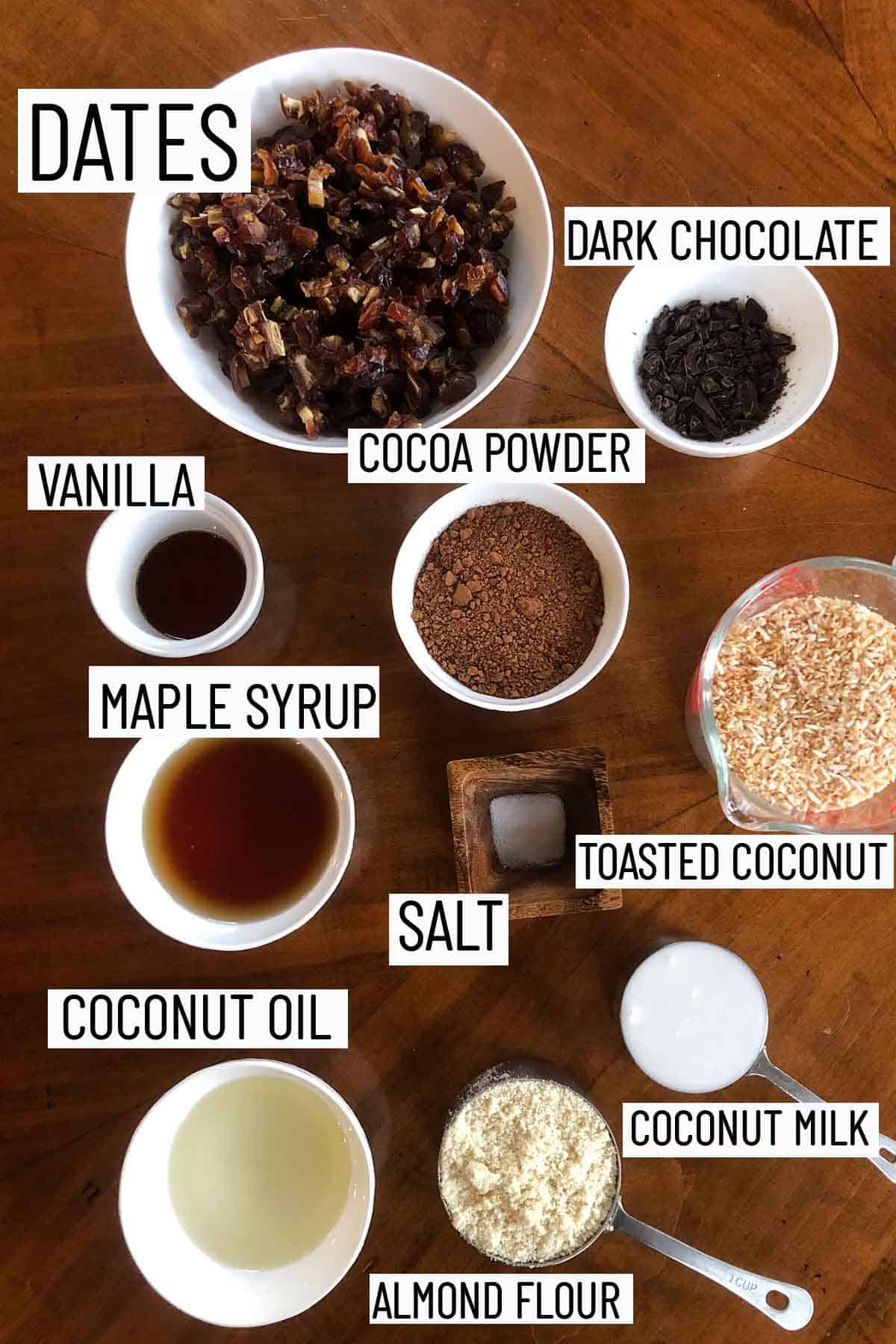Flat lay of portioned recipe ingredients including almond flour, coconut milk, coconut oil, salt, maple syrup, toasted coconut, cacao powder, vanilla, chocolate, and dates.