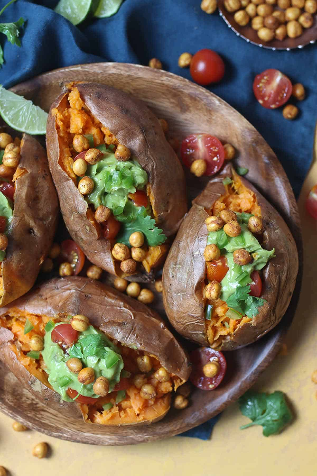 Birds eye view of four avocado stuffed sweet potatoes with guacamole and crispy chickpeas and garnished with cilantro.