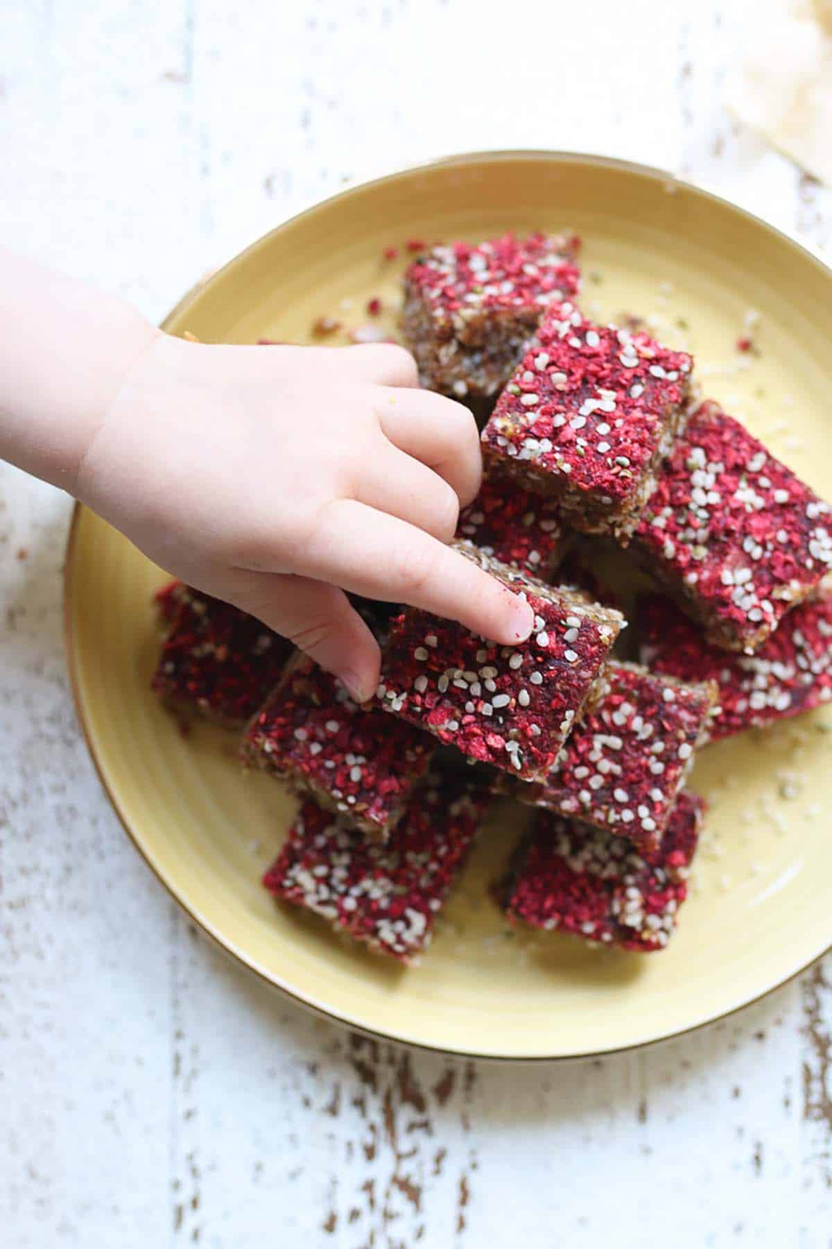 Birds eye view of granola bars on a yellow plate with a babies hand reaching for one.