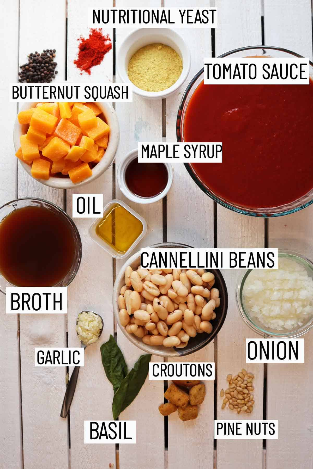 Flat lay image of portioned recipe ingredients including tomato sauce, broth, maple syrup, onion, garlic, white beans, butternut squash, nutritional yeast, basil, and croutons.