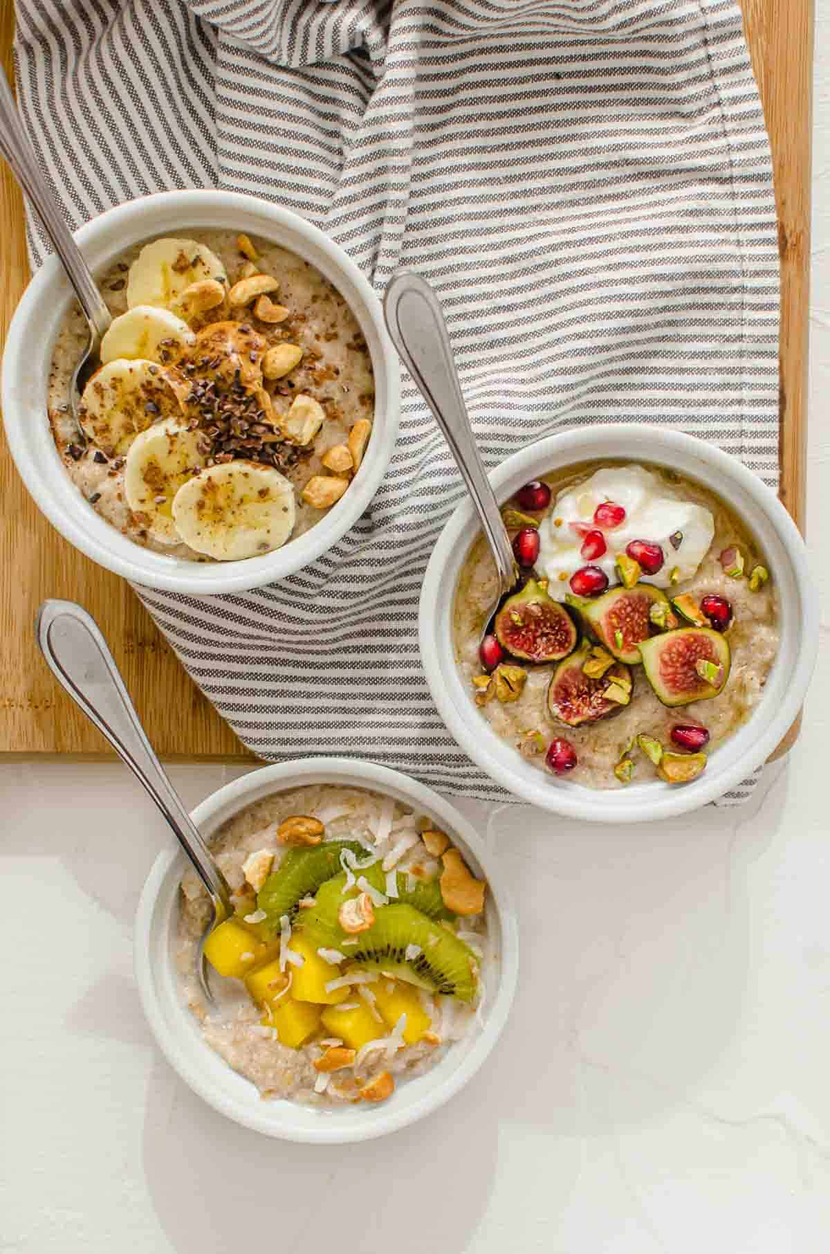 Birds eye view of three protein oatmeal bowls with different topping variations.
