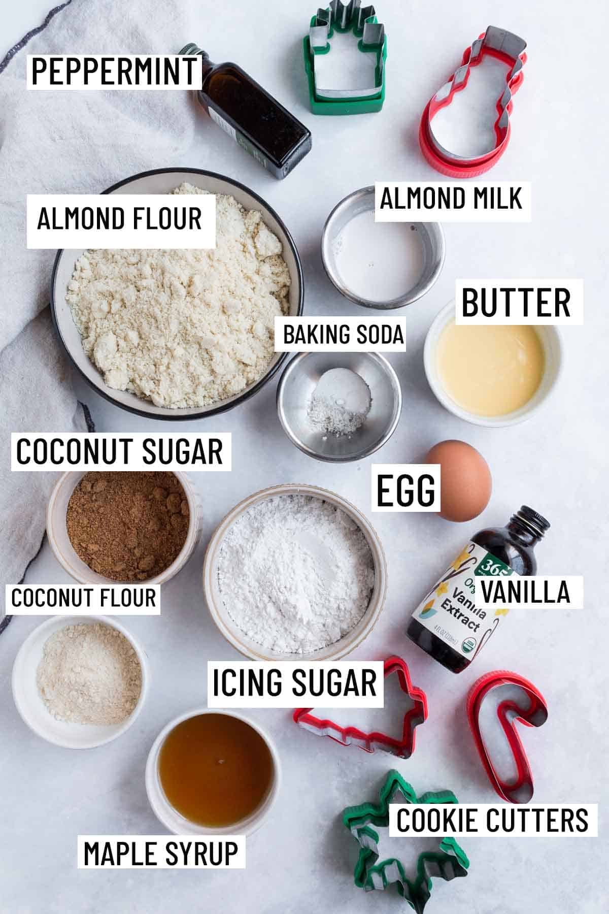 Birds eye view image of portioned ingredients for Christmas recipe including almond flour, vanilla and peppermint extract, butter, baking soda, almond milk, egg, coconut sugar, icing sugar, coconut flour, maple syrup, and cookie cutters.