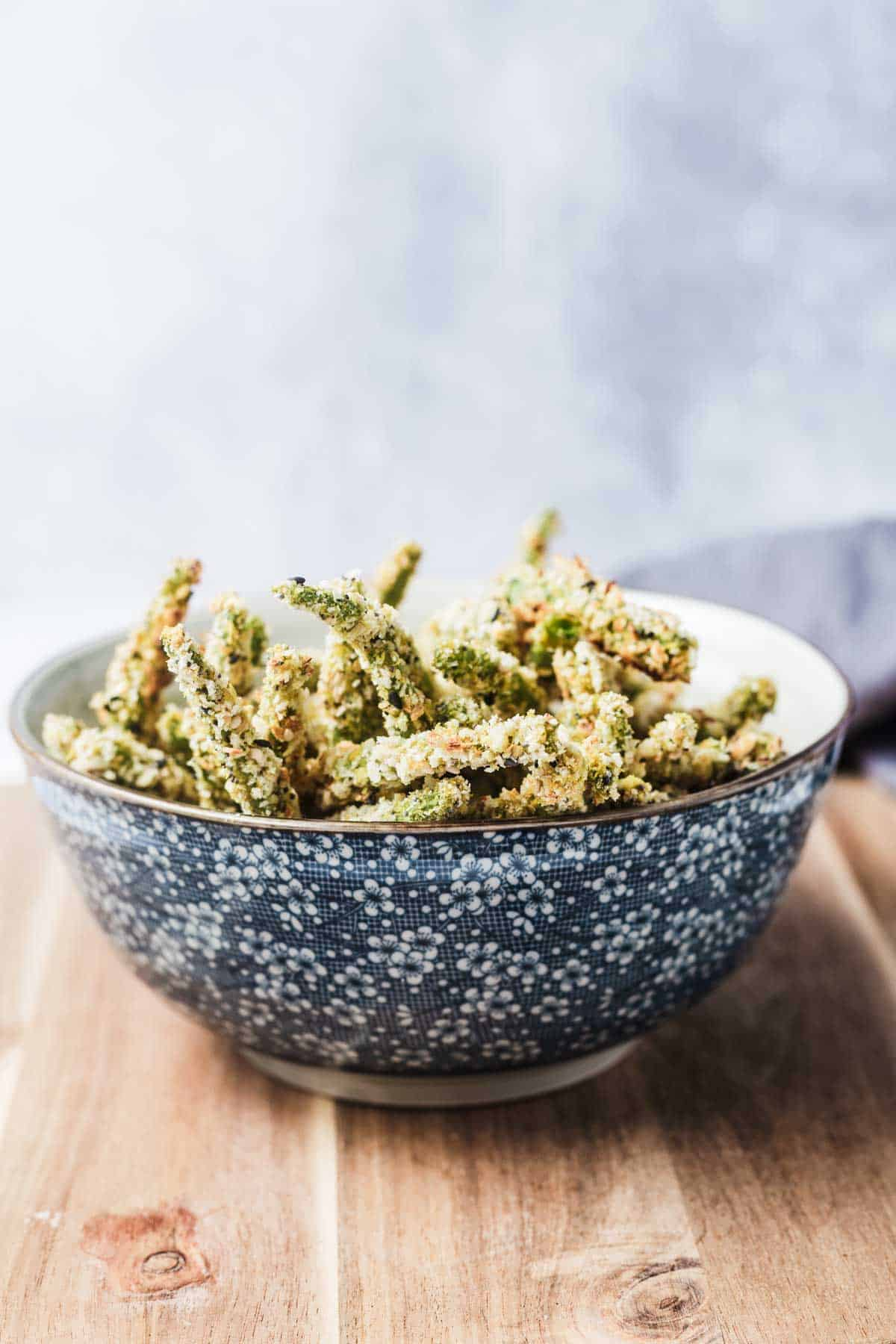 Several green bean fries in a blue floral bowl.