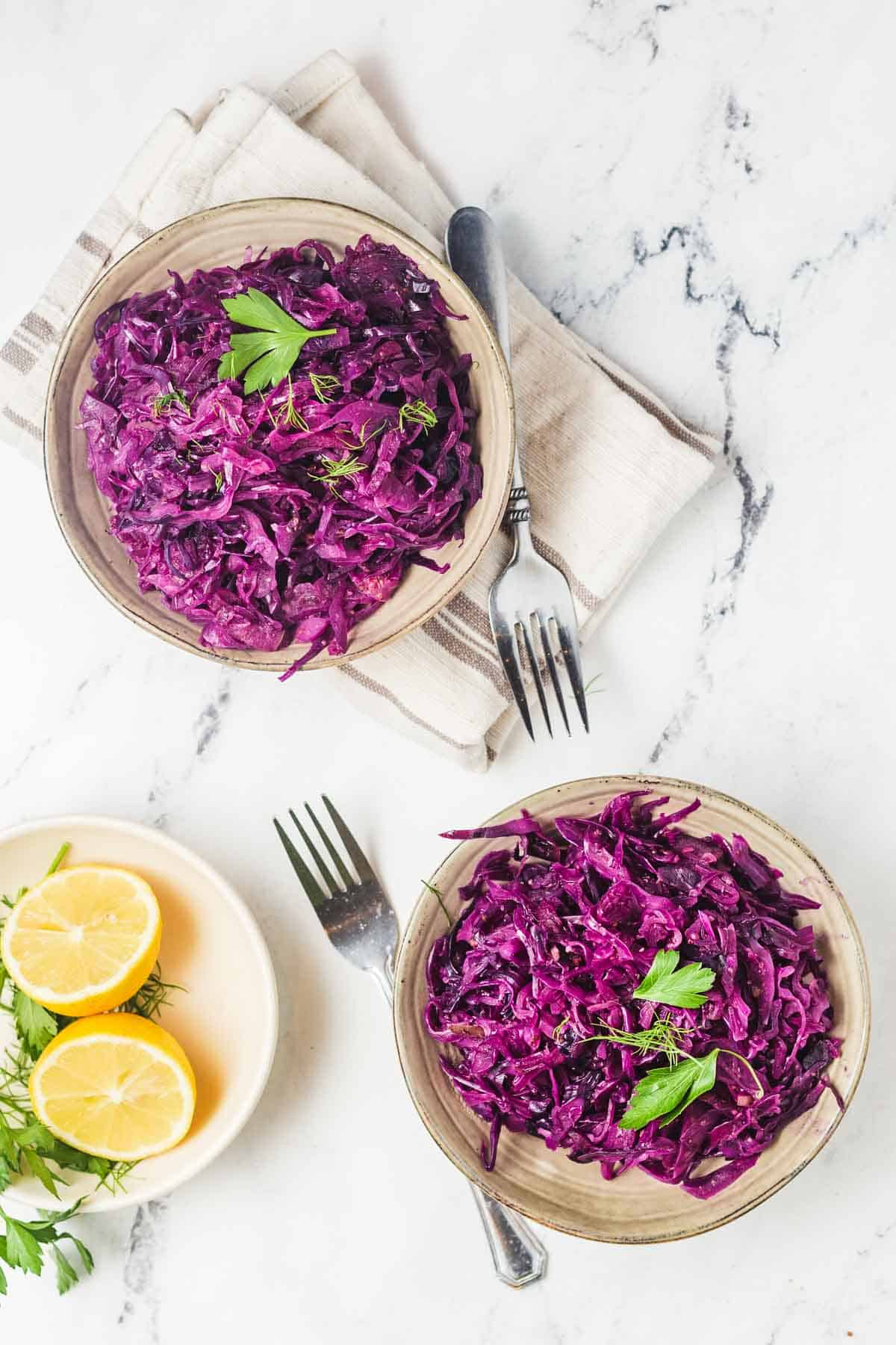 Birds eye view of two servings of instant pot cabbage in brown coloured bowls and garnished with parsley with a halved lemon on the side.