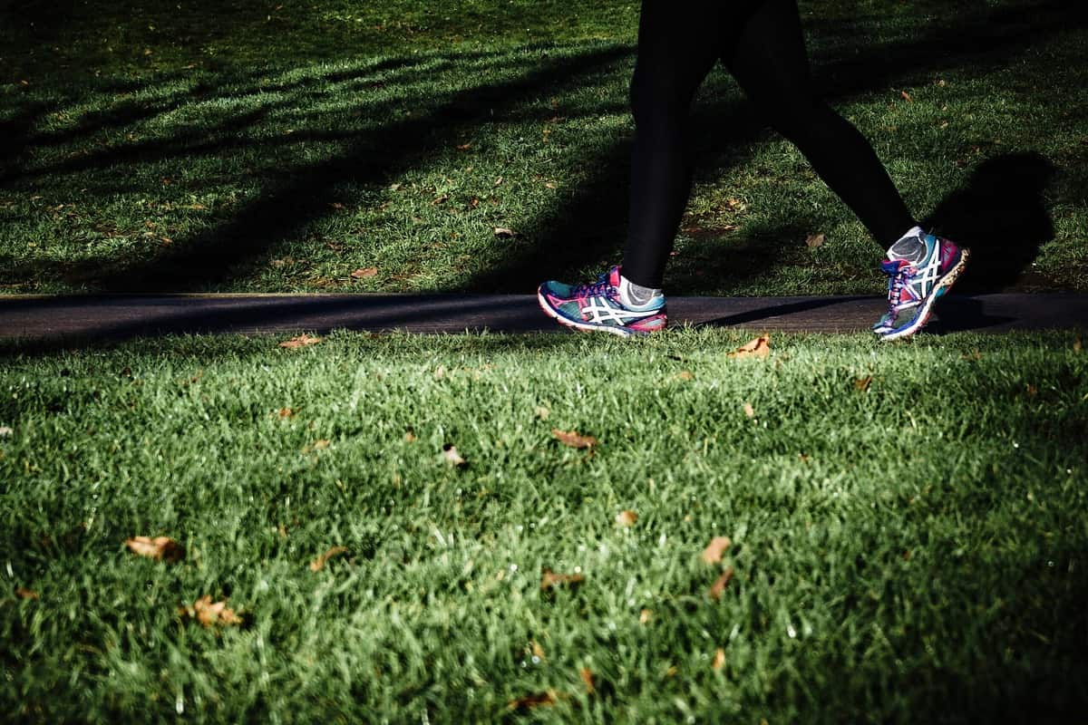 A person wearing colourful running shoes and walking outside to minimize weight gain on period.
