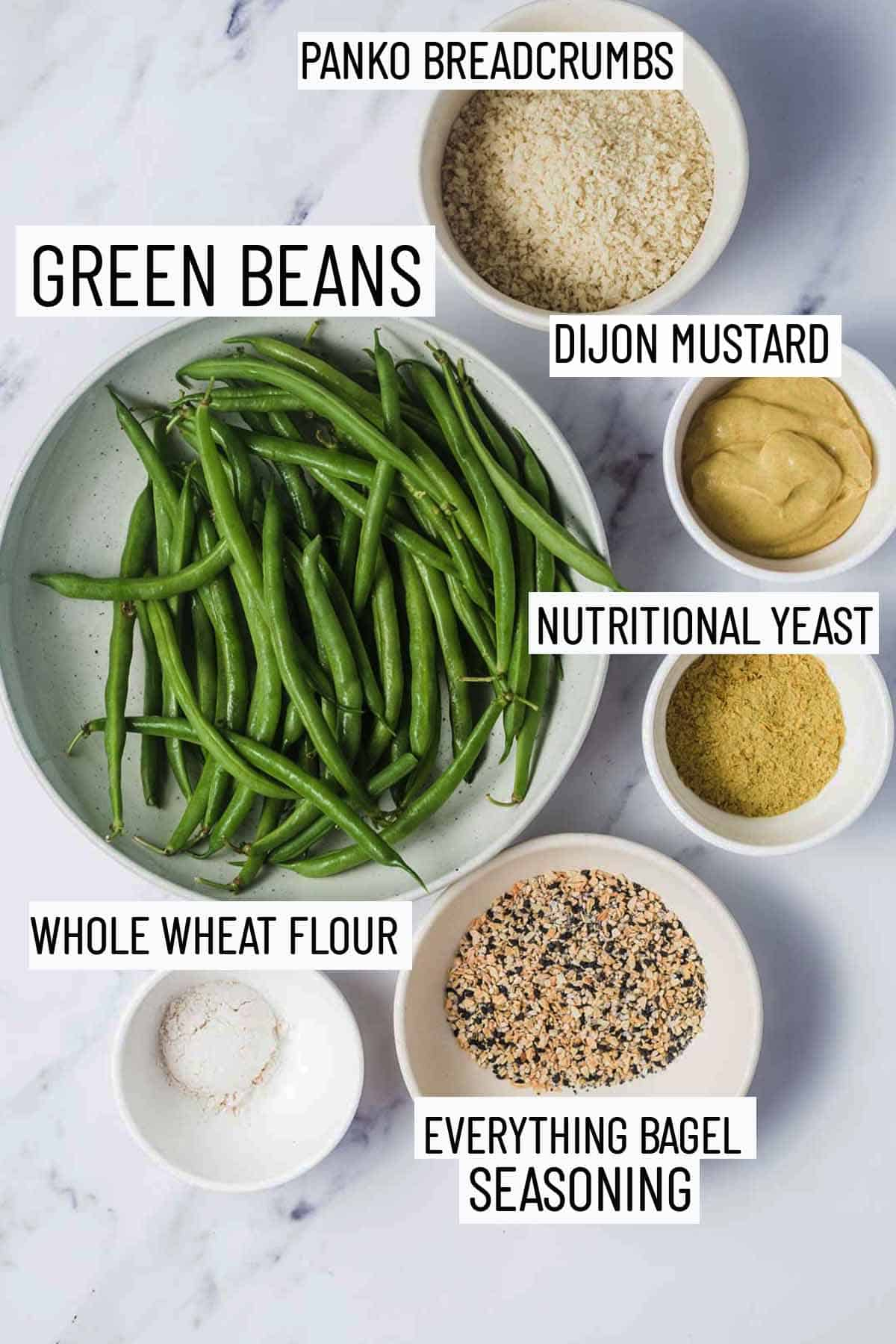 Flat lay image of portioned recipe ingredients including green beans, panko breadcrumbs, dijon mustard, nutritional yeast, everything bagel seasoning, and whole wheat flour.