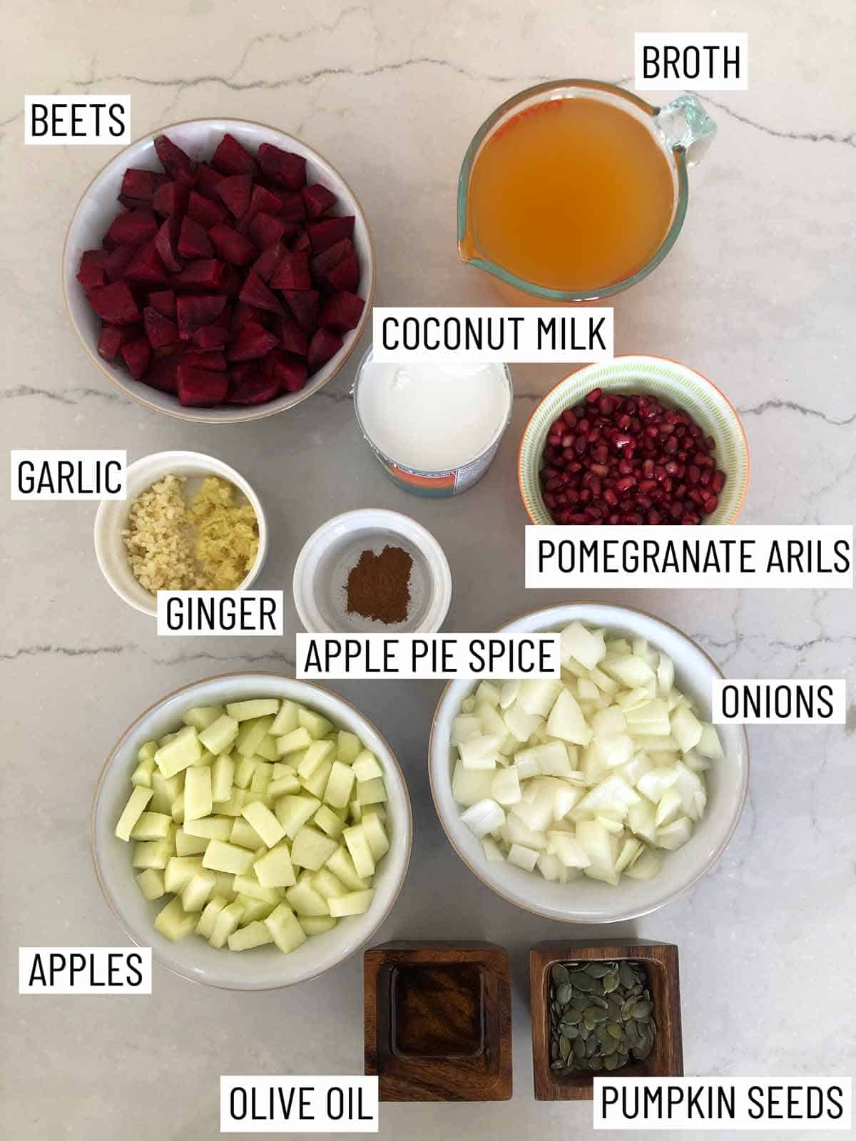 Overhead image of ingredients: broth, coconut milk, pomegranate arils, onions, pumpkin seeds, olive oil, apples, apple pie spice, ginger, garlic, and beets.