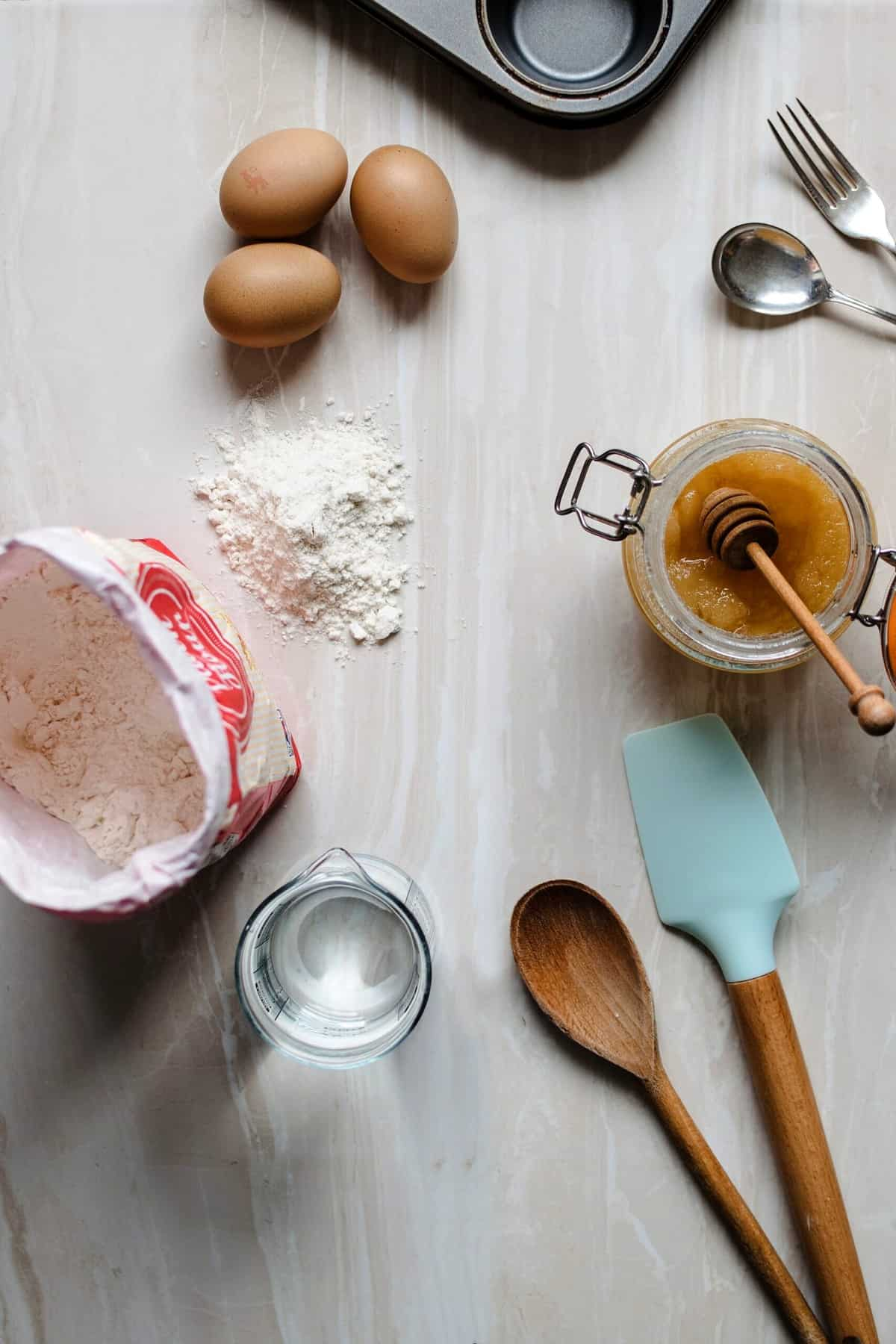 Birds eye view of baking ingredients including eggs, flour, and wooden spoons and spatulas.