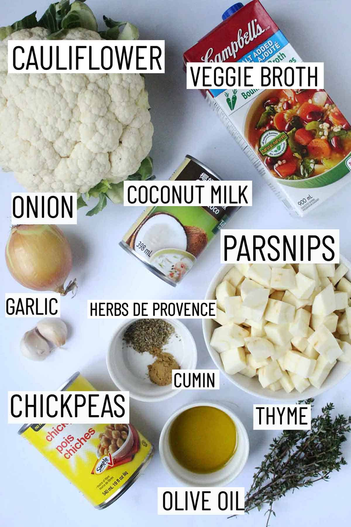 Flat lay image of recipe ingredients including thyme, olive oil, chickpeas, spices, cauliflower, parsnips, coconut milk, garlic, onion, and broth.