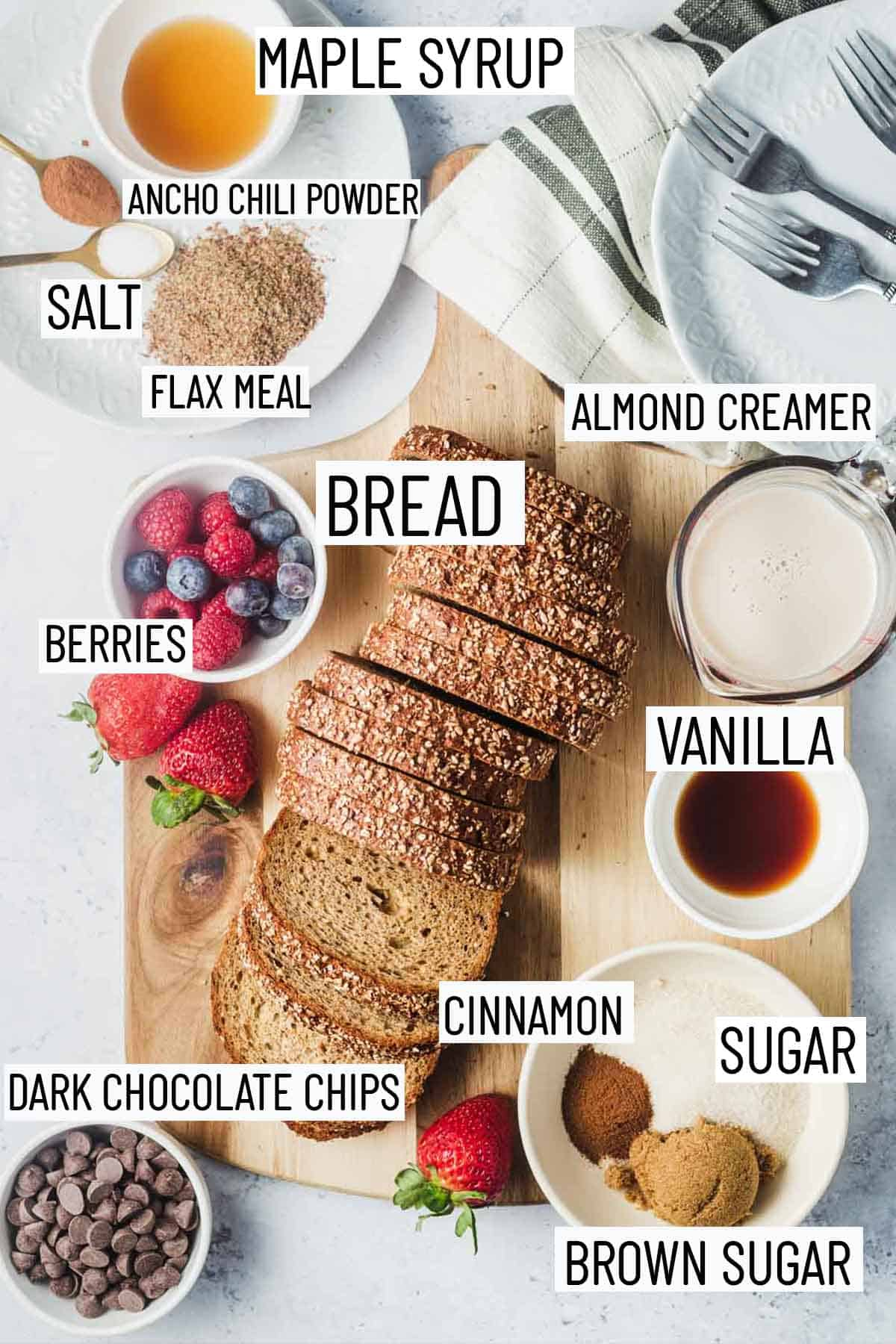 Flat lay image of portioned ingredients including sugar, vanilla, almond creamer, dark chocolate, bread, berries, flax seed, salt, ancho chili powder, maple syrup.