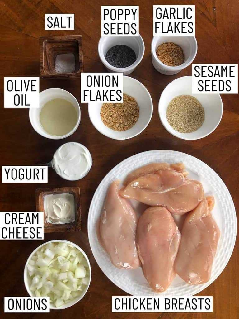 Overhead image of ingredients for everything bagel chicken breasts: chicken breasts, onions, cream cheese, yogurt, olive oil, salt, poppy seeds, garlic flakes, onion flakes, sesame seeds.