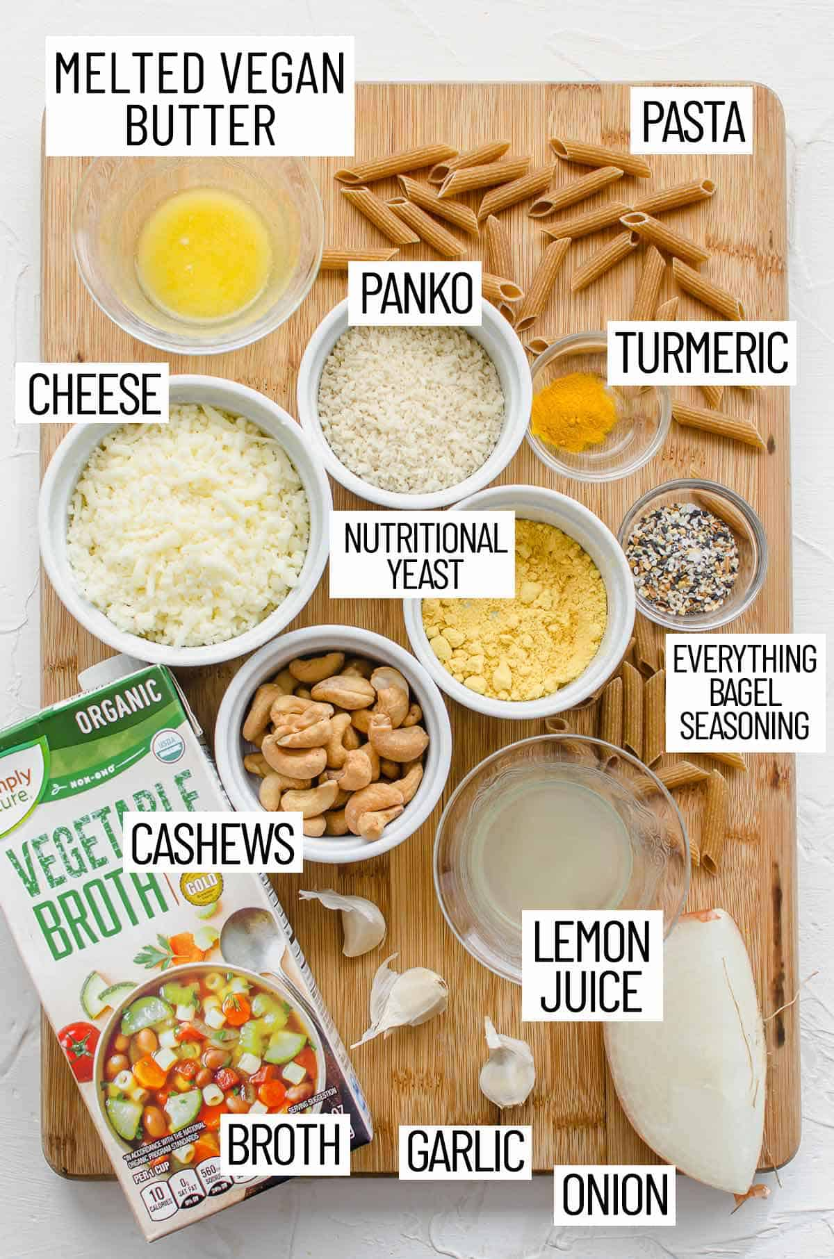 Overhead photo of ingredients for everything bagel mac and cheese including broth, garlic onion, lemon juice, everything bagel seasoning, nutritional yeast, cheese, panko, turmeric, pasta, and melted butter.