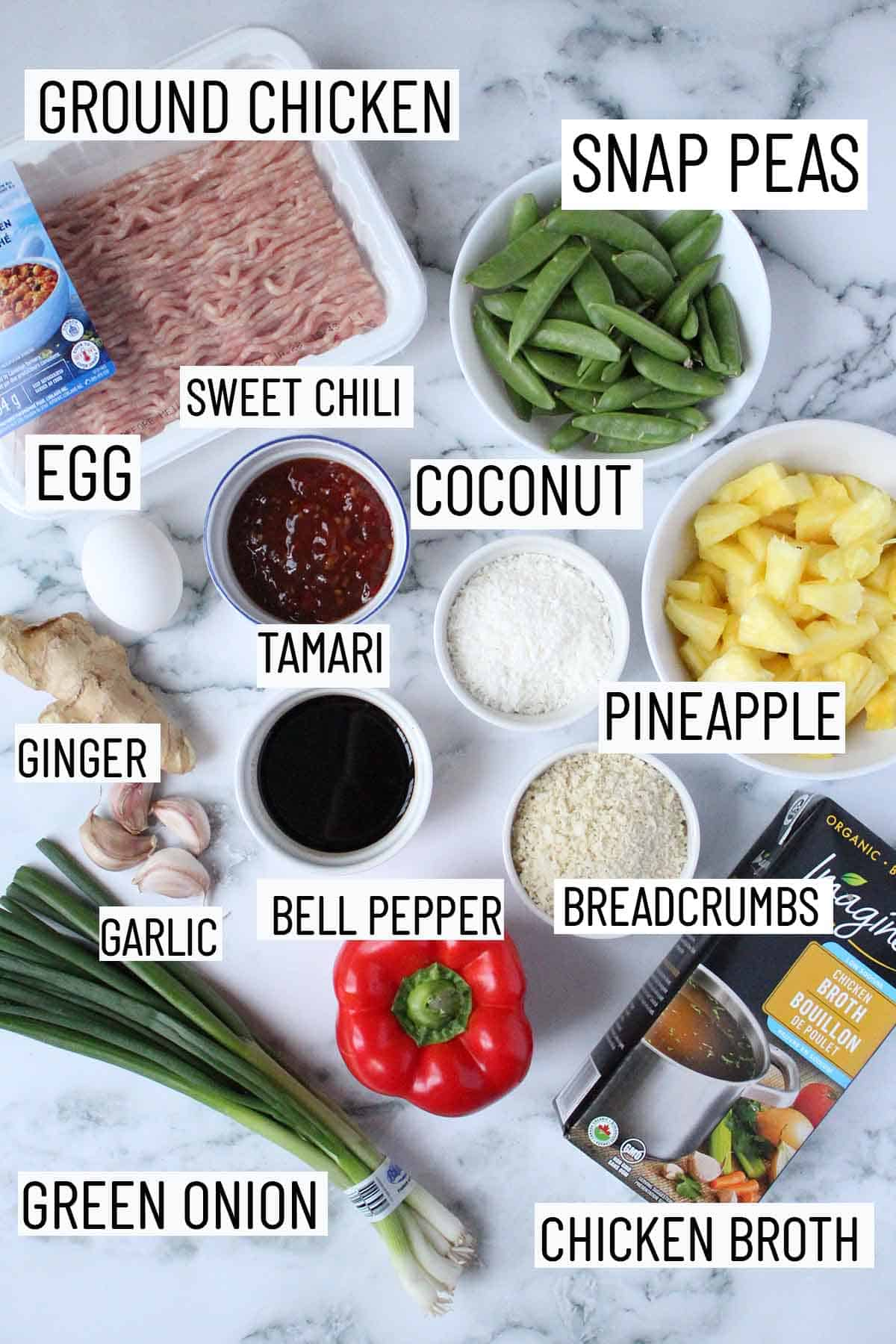 Flat lay image of portioned recipe ingredients including snap peas, ground chicken, sweet chili sauce, coconut, pineapple, tamari, egg, ginger, garlic, breadcrumbs, broth, bell pepper, and green onion.