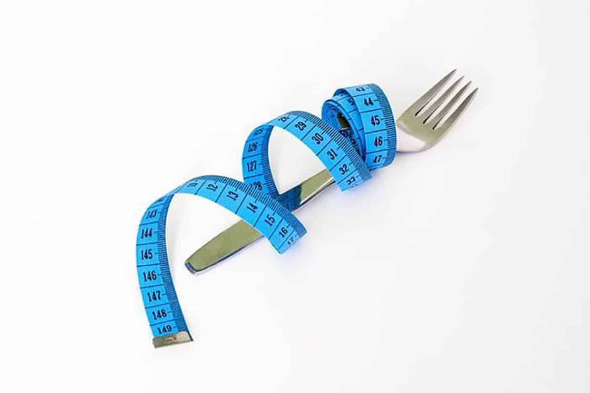 Measuring tape wrapped around a silver fork for weight loss.