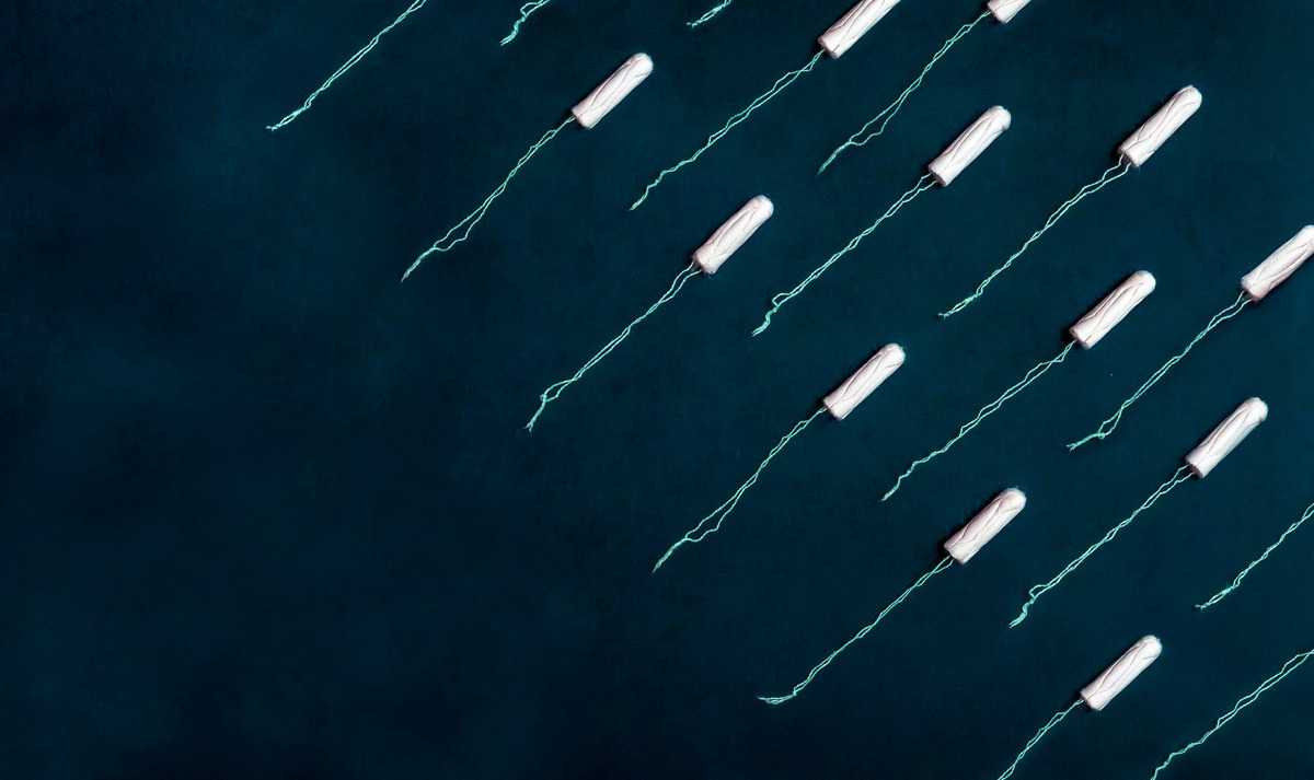 Several period tampons laid out against a dark blue background.