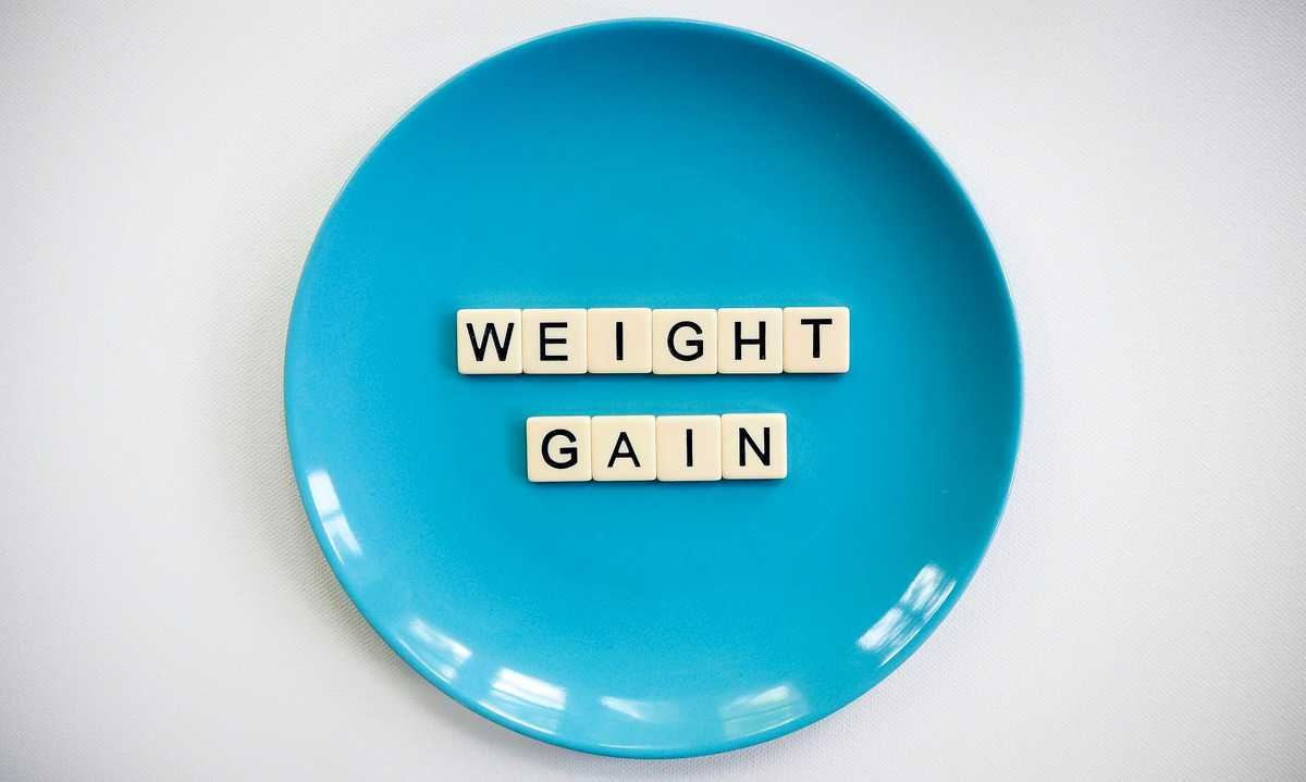 """A blue plate with the words """"weight gain"""" written in tiles."""