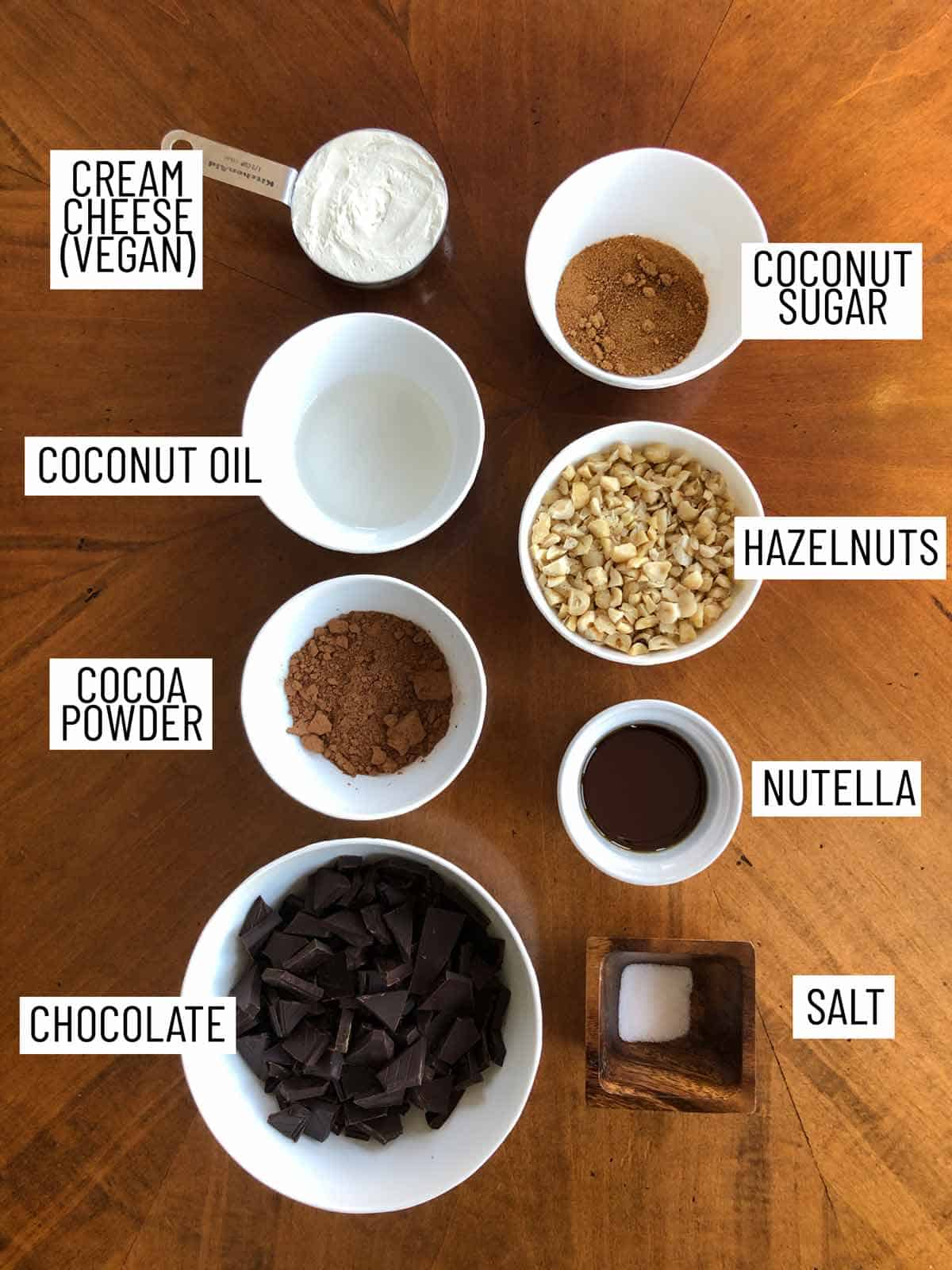 Overhead image of ingredients for no bake nutella cheesecake cups: cream cheese, coconut oil, cocoa powder, chocolate, salt, nutella, hazelnuts, coconut sugar.