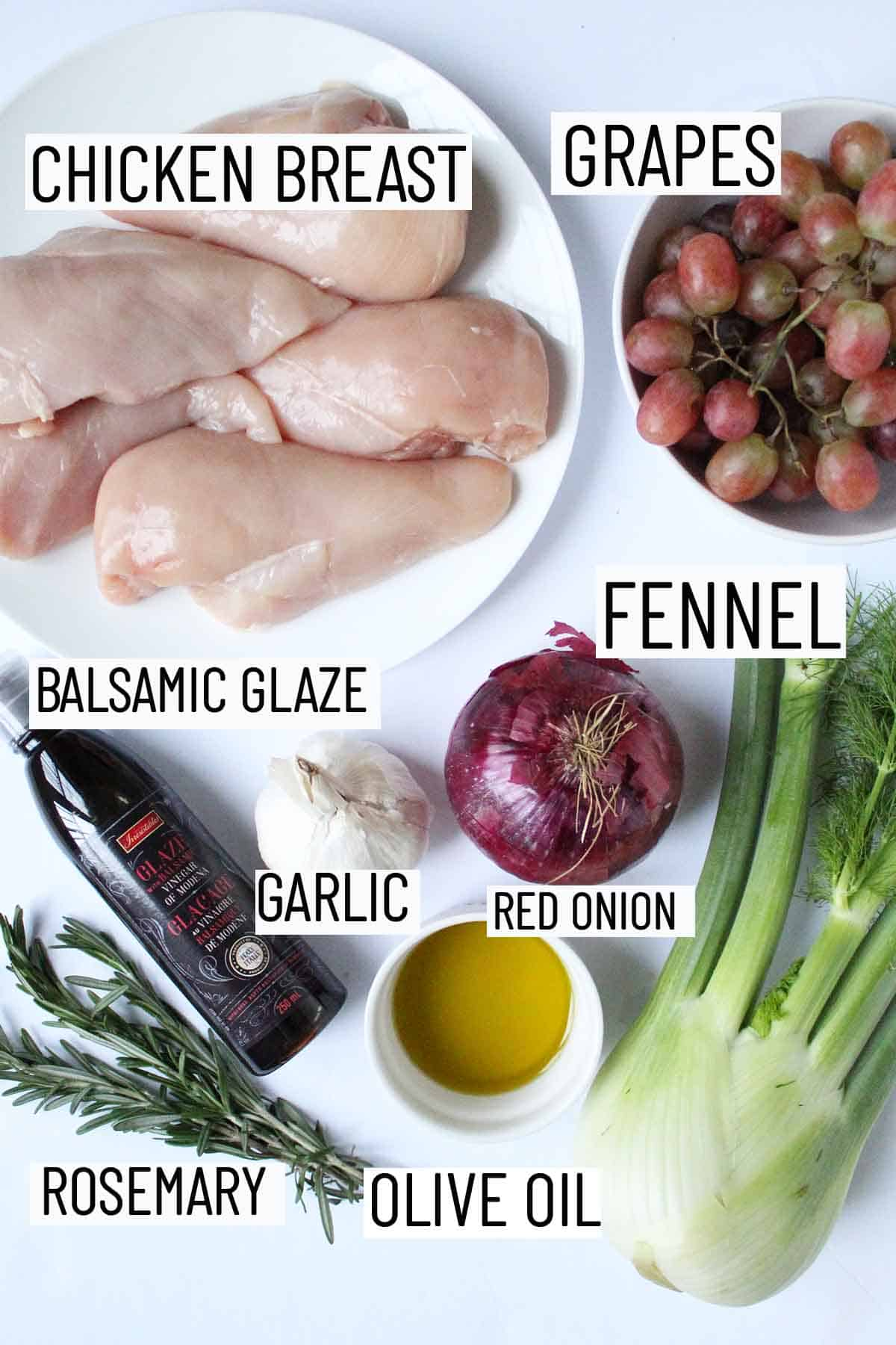 Flay lay image of recipe ingredients including chicken breast, grapes, fennel, balsamic glaze, garlic, red onion, olive oil, and rosemary.