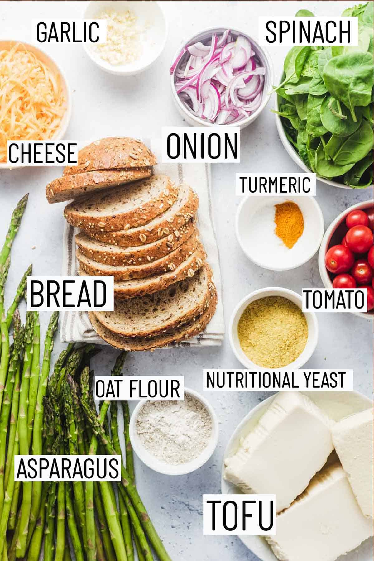 Flat lay image of recipe ingredients including bread, spinach, onion, garlic, cheese, oat flour, tofu, asparagus, nutritional yeast, tomato, and turmeric.