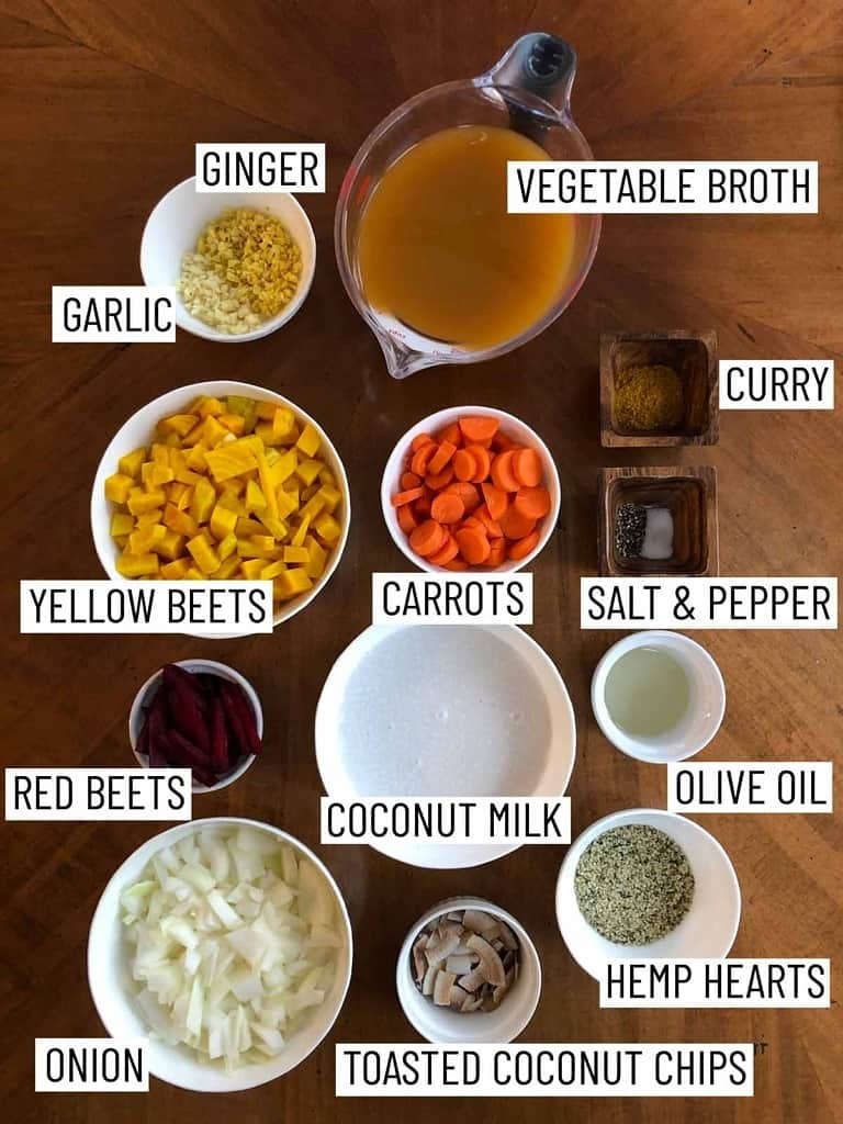 Overhead photo of ingredients for a vegan curry including vegetable broth, curry, salt and pepper, olive oil, hemp hearts, toasted coconut chips, onion, red beets, yellow beets, coconut milk, carrots, garlic, and ginger.