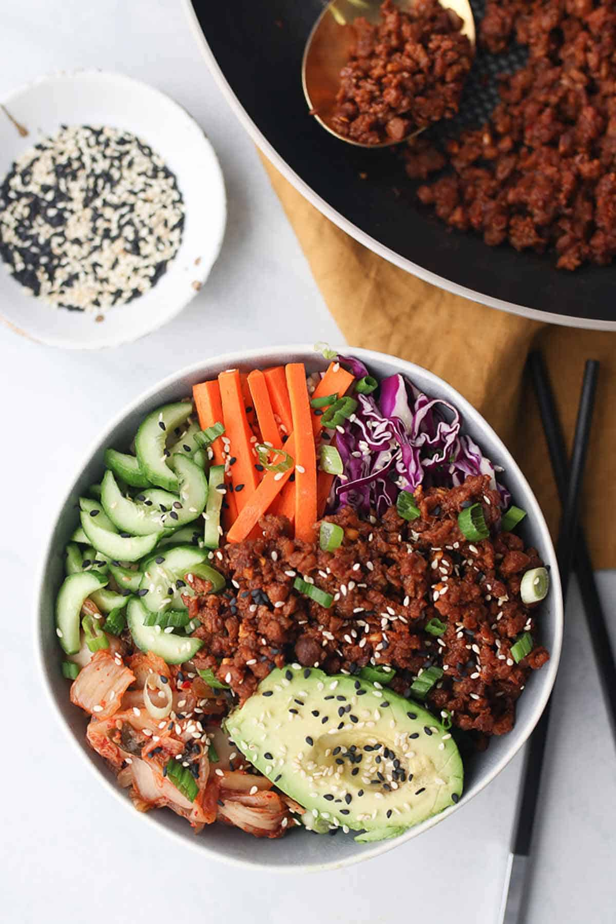 Birds eye view of vegan buddha bowl garnished with green onion and sesame seed with a bowl of sesame seeds in the background and two chopsticks laying on the side.