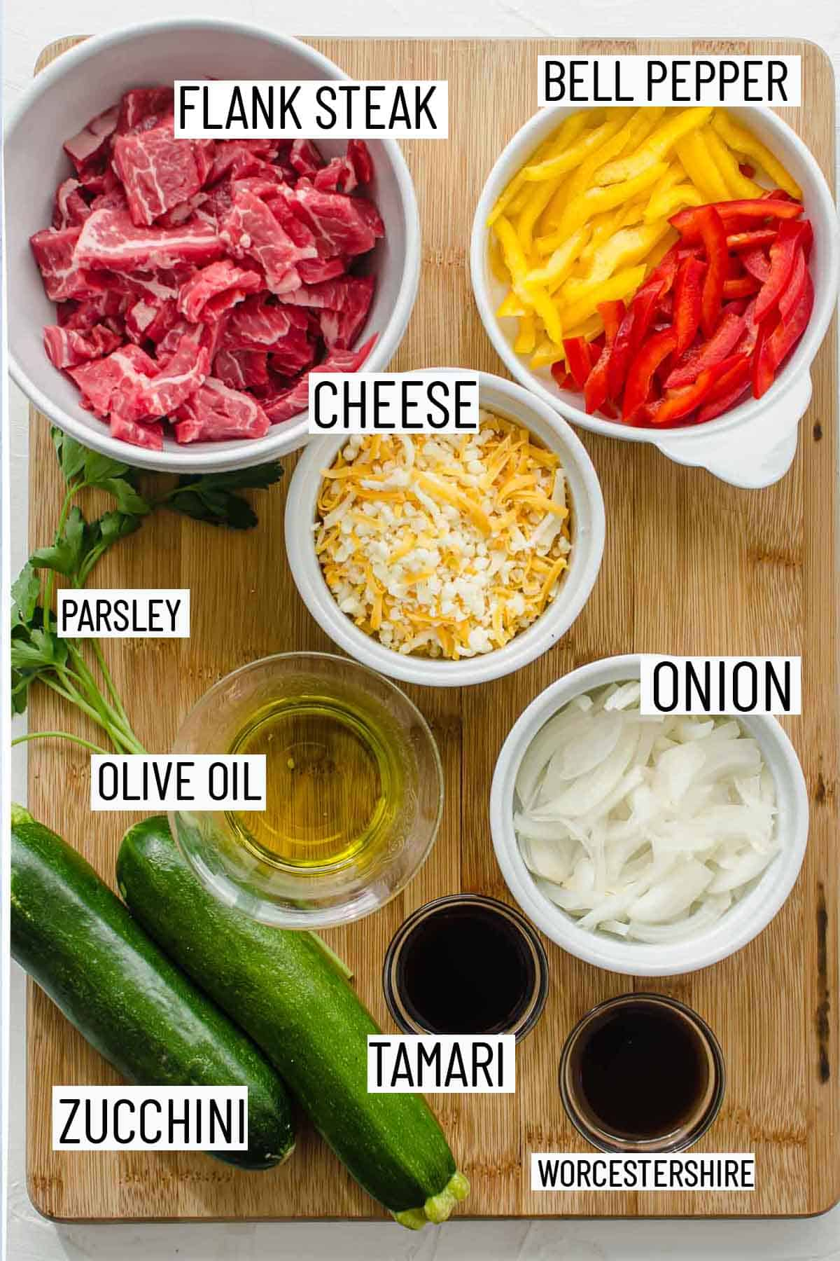Flat lay of portioned ingredients for zucchini boats including steak, bell pepper, cheese, parsley, onion, olive oil, zucchini, tamari and worestershire sauce.