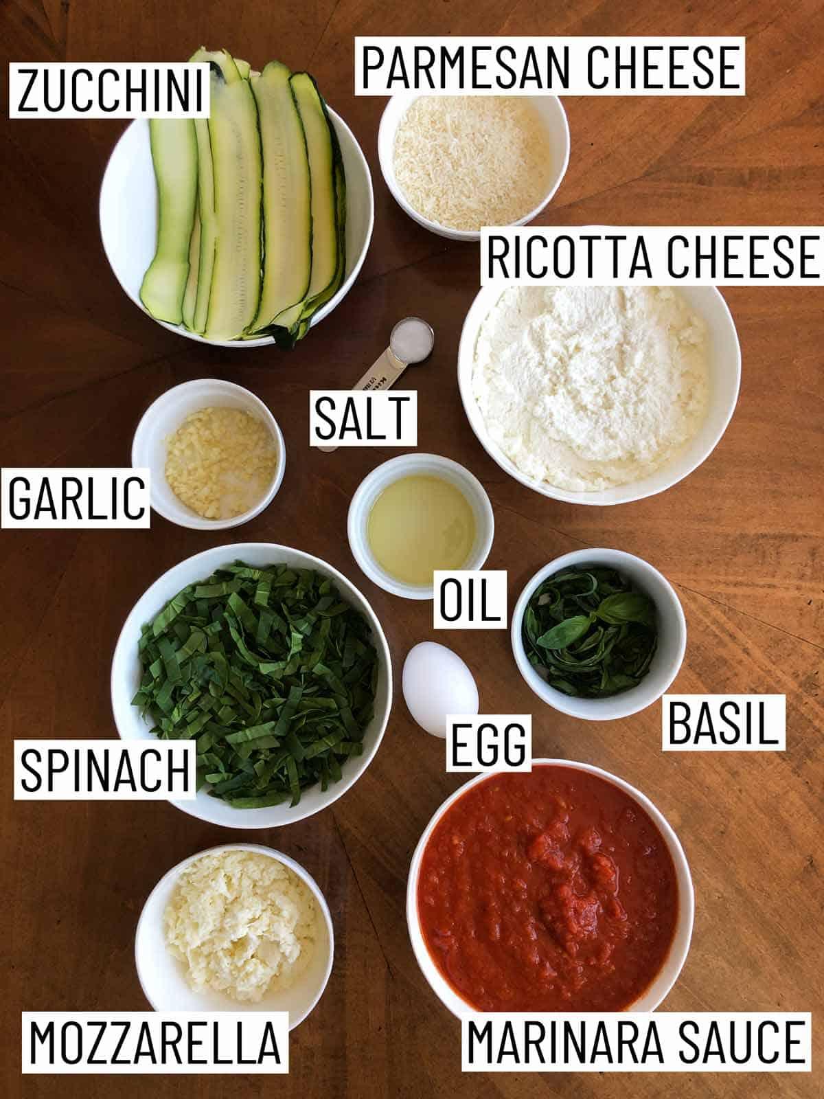 Overhead image of ingredients: zucchini, parmesan cheese, ricotta cheese, salt, oil, basil, egg, marinara sauce, mozzarella, spinach, and garlic.
