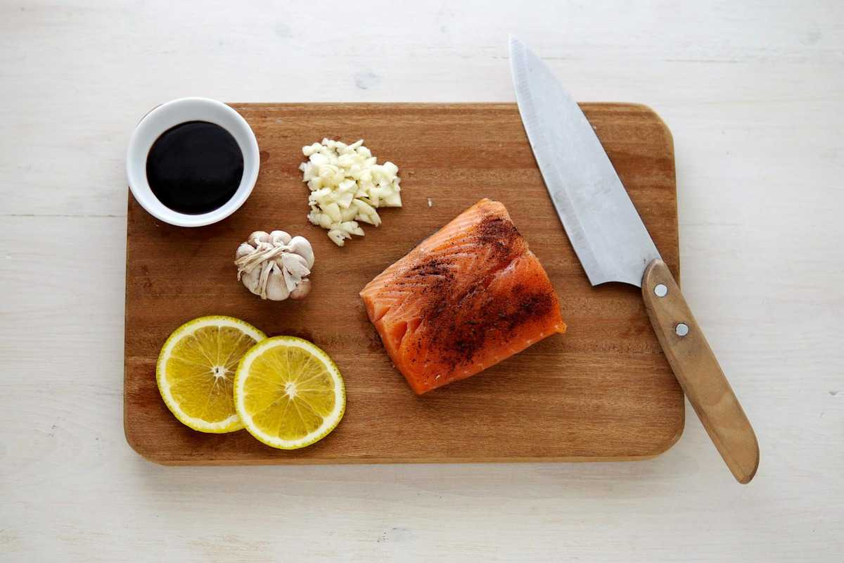 A piece of seasoned salmon, lemon slices, garlic, a chefs knife and soy sauce on a cutting board.