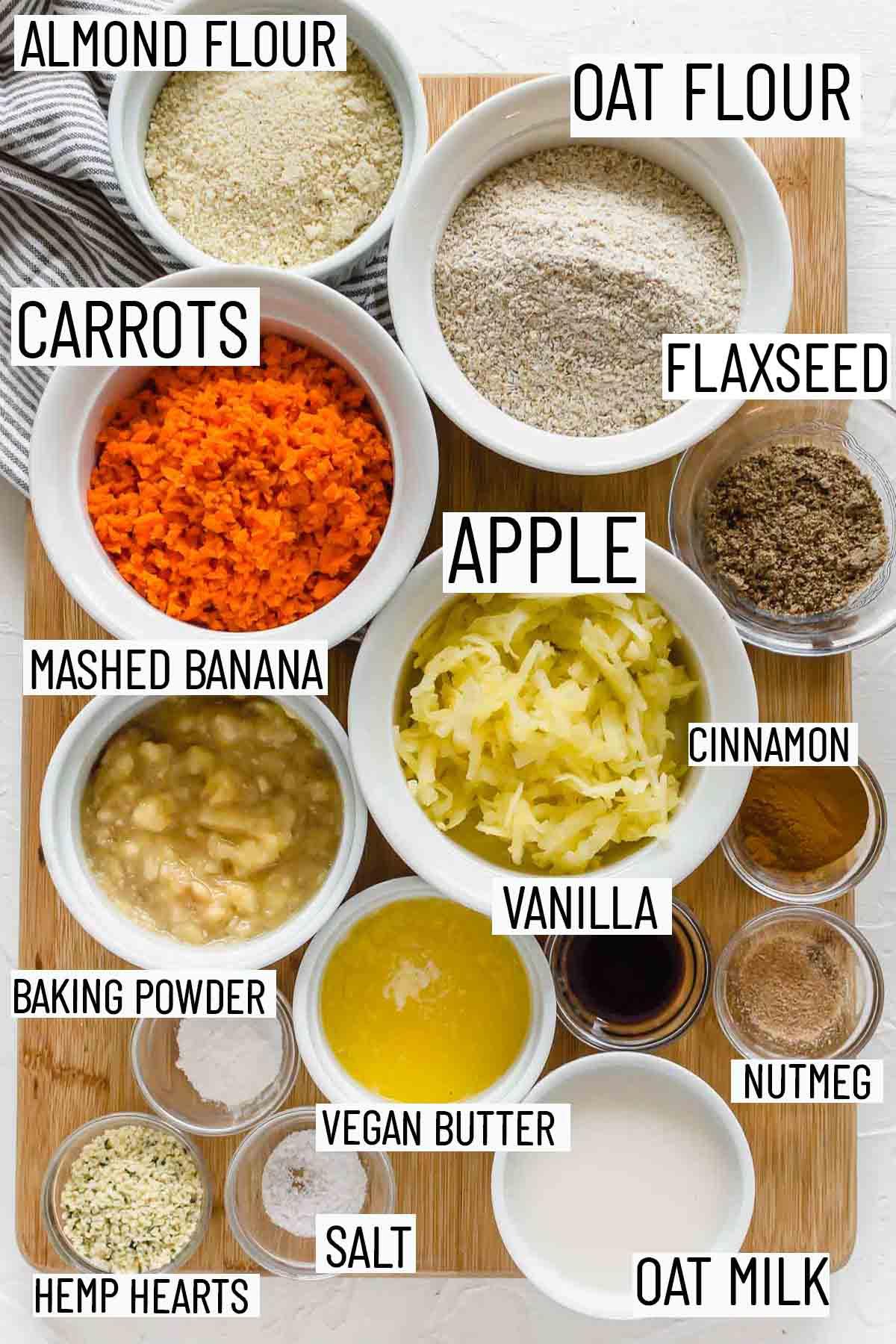 Flat lay image showing portioned recipe ingredients including oat flour, almond flour, apple, carrot, banana, baking powder, salt, hemp hearts, oat milk, nutmeg, vanilla, cinnamon, and flax seed.