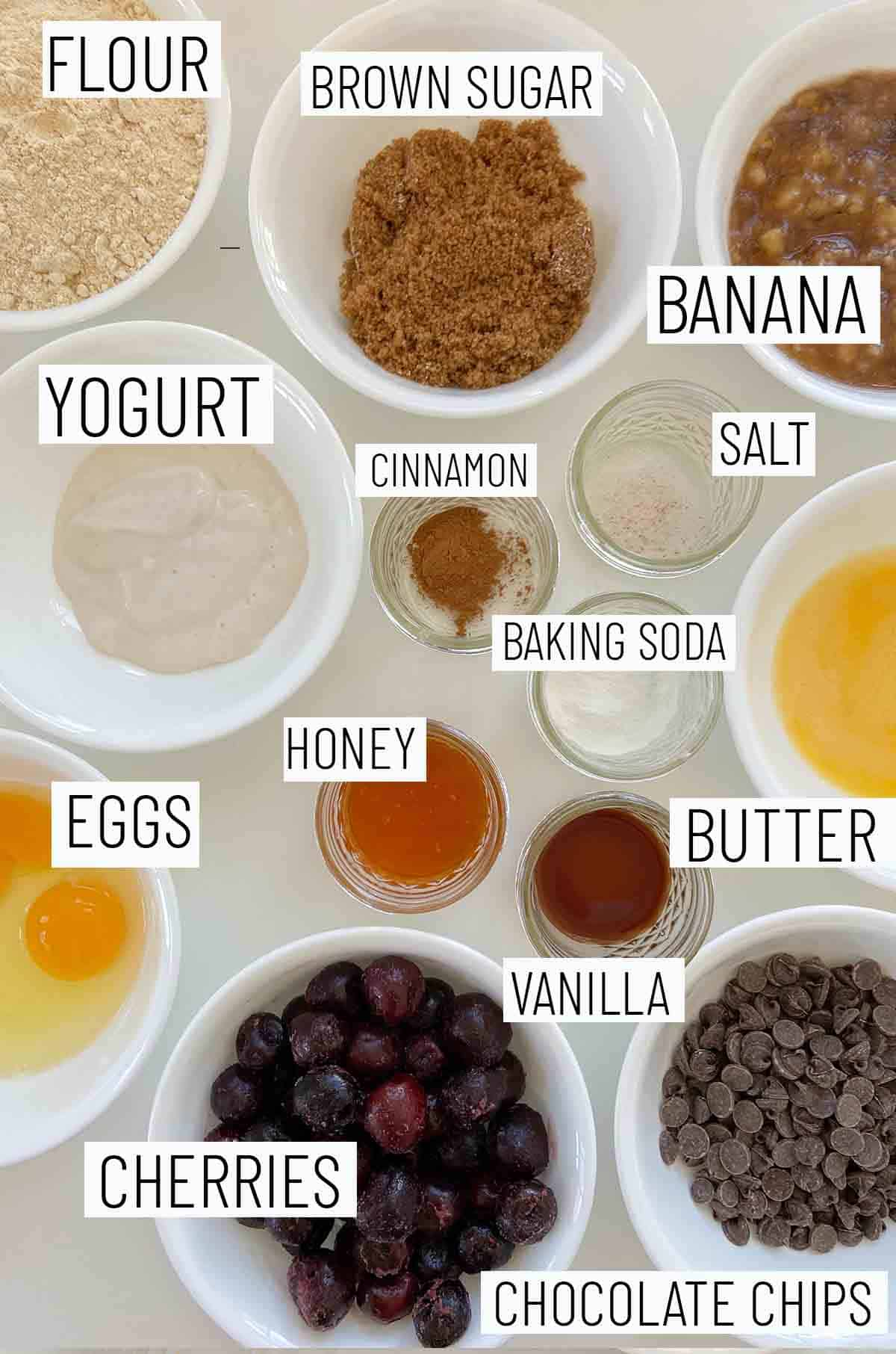 Flat lay image of portioned recipe ingredients including chocolate chips, cherries, eggs, butter, vanilla, honey, baking soda, salt, cinnamon, yogurt, banana and flour.