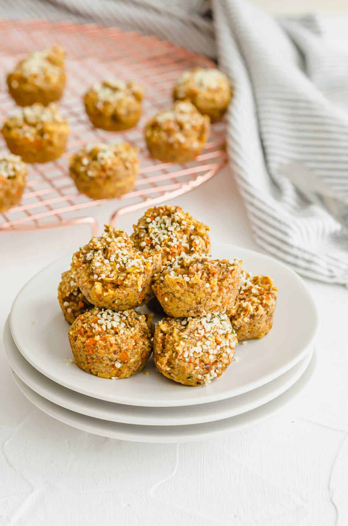 Several baby carrot muffins on a white plate with more cooling in a cooling rack in the background.
