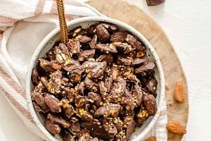 Chocolate covered almonds in a bowl on top of a serving board.