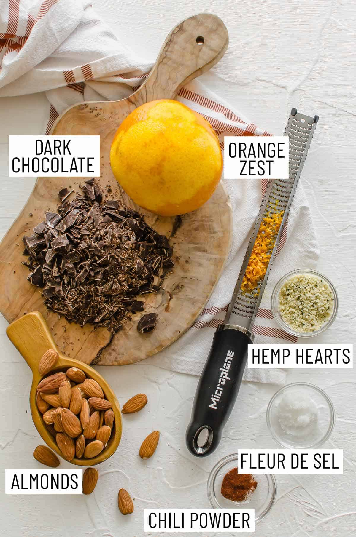 Overhead photo of ingredients needed to make recipe: dark chocolate, orange zest, hemp hearts, fleur de sel, chili powder, and almonds.