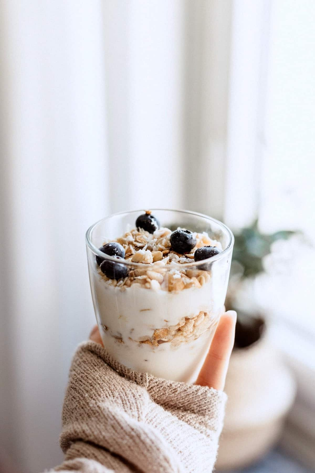 A hand holding up a breakfast parfait with blueberries and granola.