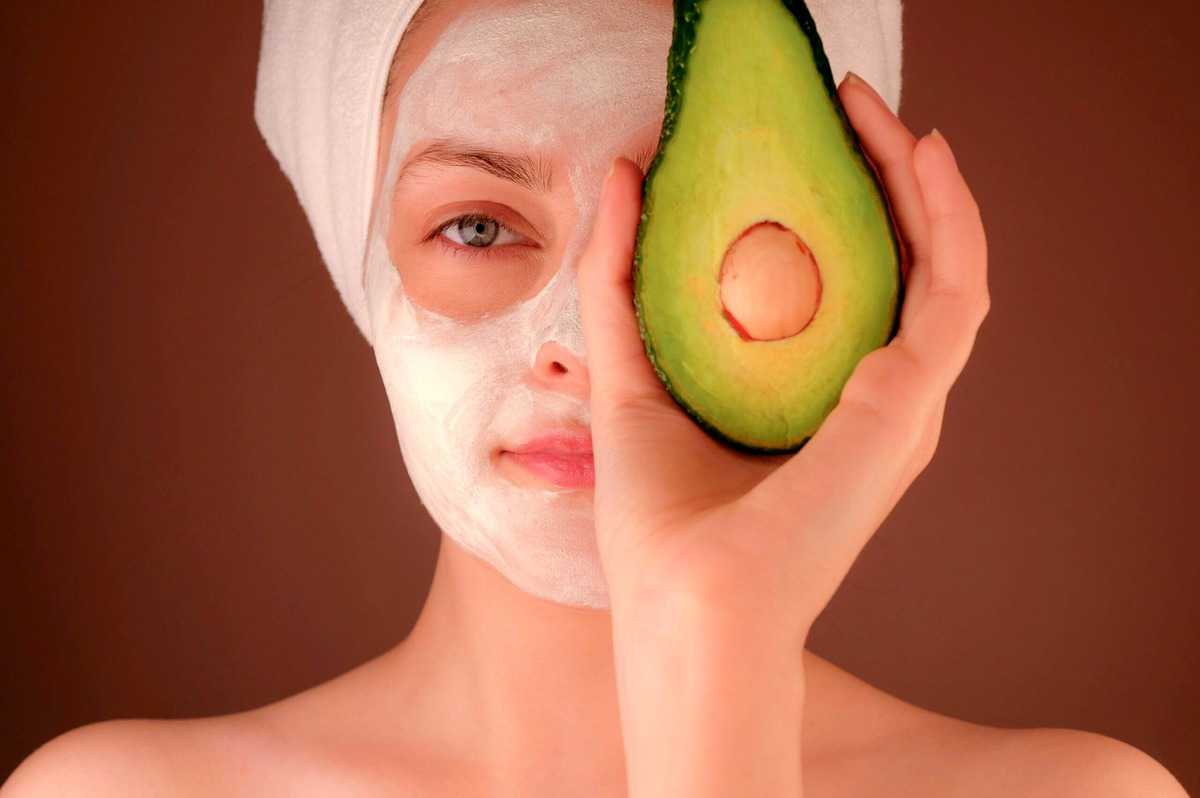 Woman with a white face mask holding up an avocado to her eye.