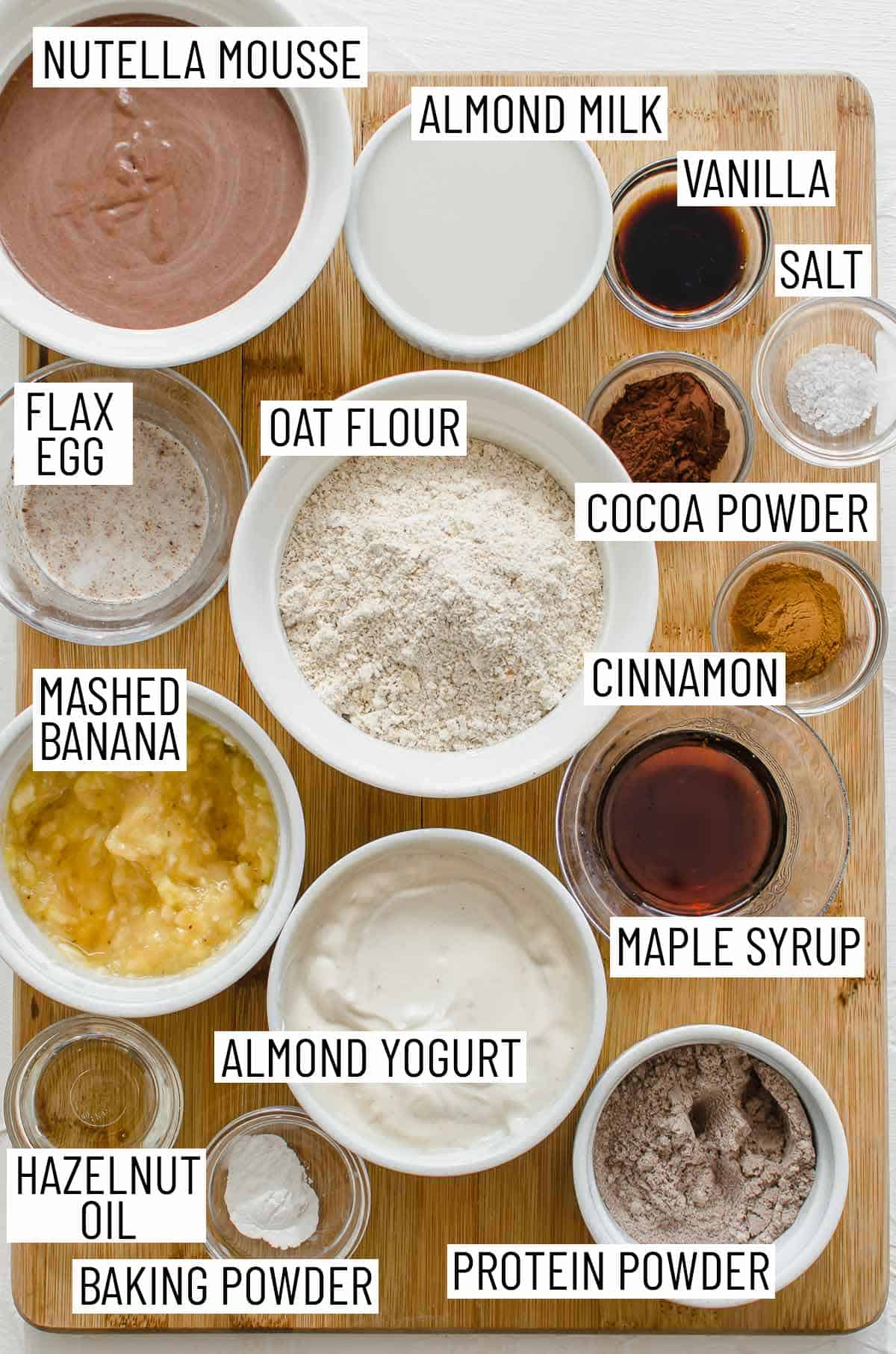 Overhead image of ingredients needed to make pancakes: mousse, almond milk, vanilla, salt, cocoa powder, cinnamon, oat flour, flax egg, mashed banana, maple syrup, almond yogurt, hazelnut oil, baking powder, and protein powder.
